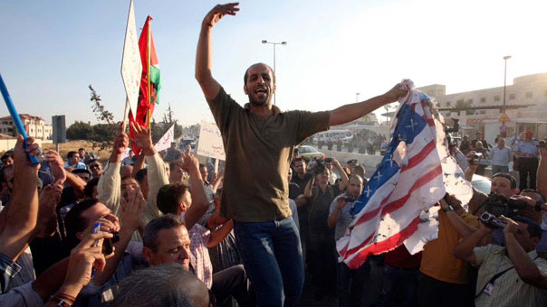 Sept. 14: Jordanian protesters chant anti U.S.A. slogans and burn the American and the Israeli flags in front of the U.S. embassy in Amman, Jordan.