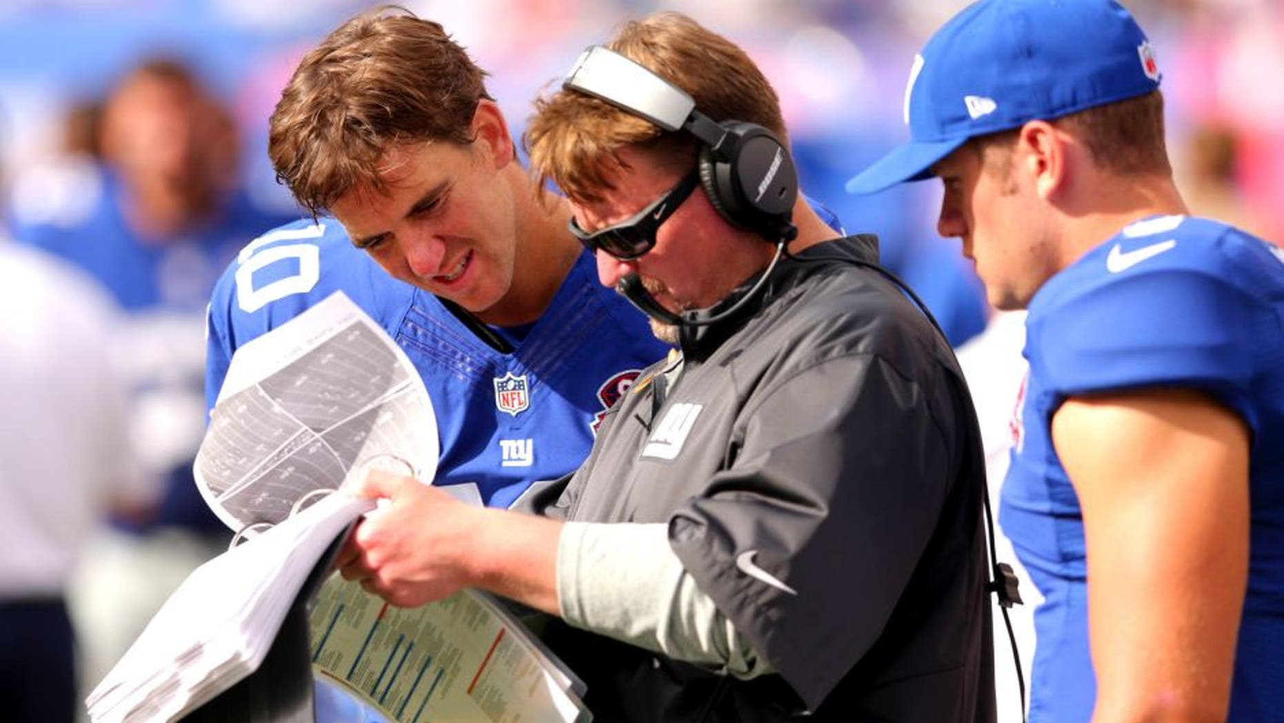 Sep 14, 2014; East Rutherford, NJ, USA; New York Giants quarterback Eli Manning (10) and offensive coordinator Ben McAdoo and New York Giants quarterback Ryan Nassib (9) looks at the playbook during the fourth quarter against the Arizona Cardinals at MetLife Stadium. The Cardinals defeated the Giants 25-14. Mandatory Credit: Brad Penner-USA TODAY Sports