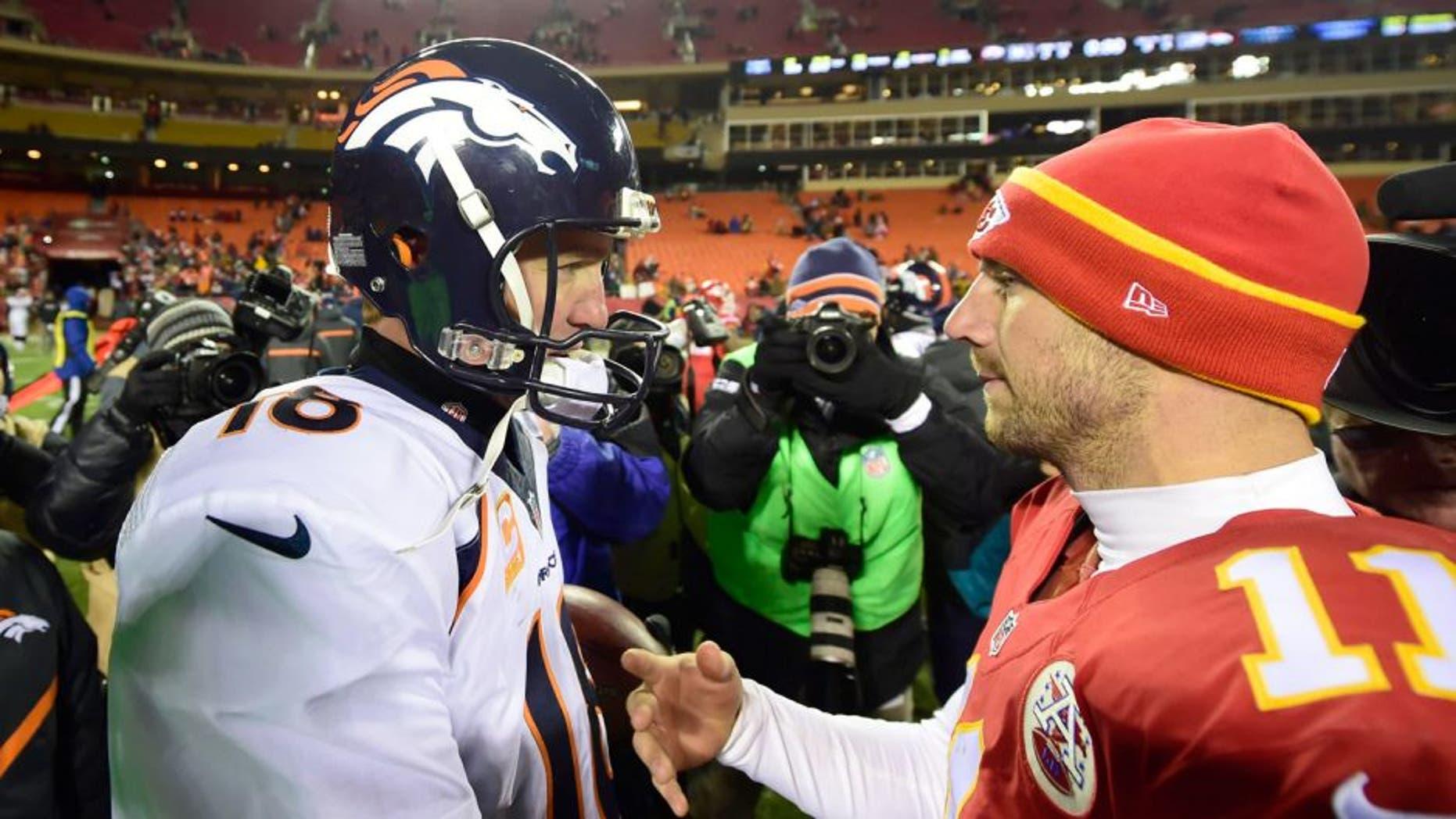 Nov 30, 2014; Kansas City, MO, USA; Denver Broncos quarterback Peyton Manning (18) greets Kansas City Chiefs quarterback Alex Smith (11) following the game at Arrowhead Stadium. The Broncos defeated the Chiefs 29-16. Mandatory Credit: Ron Chenoy-USA TODAY Sports