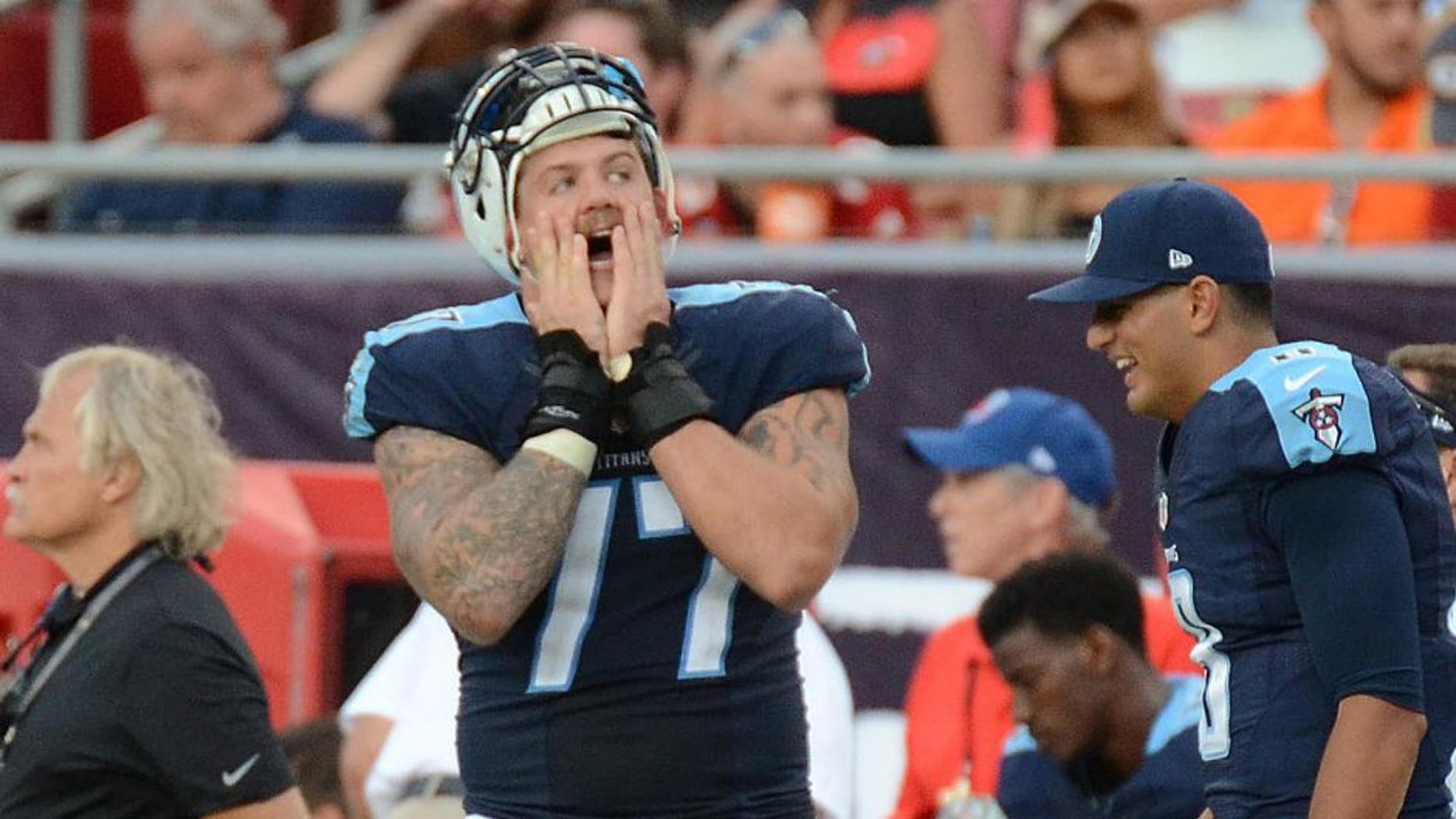 Sep 13, 2015; Tampa, FL, USA; Tennessee Titans quarterback Marcus Mariota (8) and linemen Taylor Lewan (77) react on the sideline in the second half during their game against the Tampa Bay Buccaneers at Raymond James Stadium. The Titans defeated the Buccaneers 42-14. Mandatory Credit: Jonathan Dyer-USA TODAY Sports