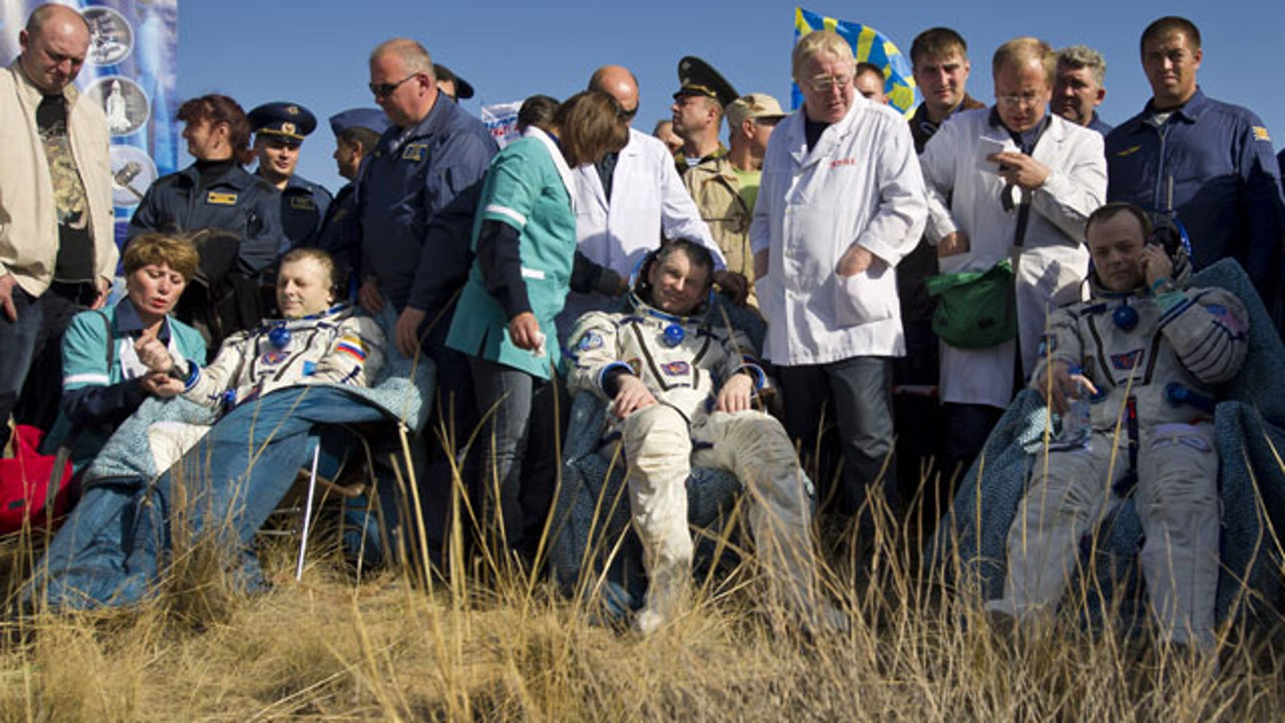 In this image provided by NASA Expedition 28 Commander Andrei Borisenko, left, Flight Engineers Alexander Samokutyayev, center, and Ron Garan, sit in chairs outside the Soyuz Capsule just minutes after they landed in a remote area outside the town of Zhezkazgan, Kazakhstan.