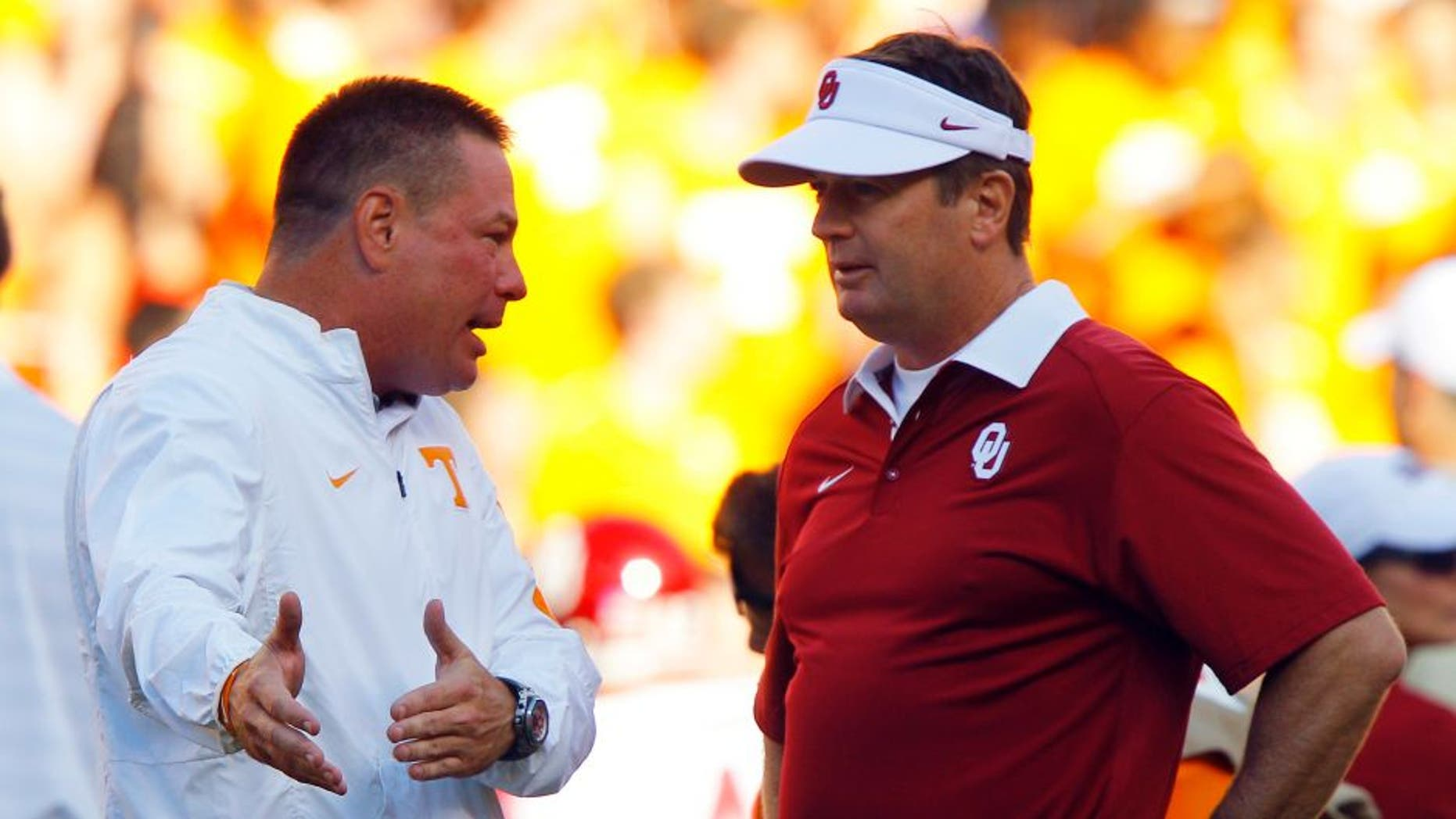 Tennessee head coach Butch Jones, left, talks with Oklahoma head coach Bob Stoops before an NCAA college football game, Saturday, Sept. 12, 2015 in Knoxville, Tenn. (AP Photo/Wade Payne)