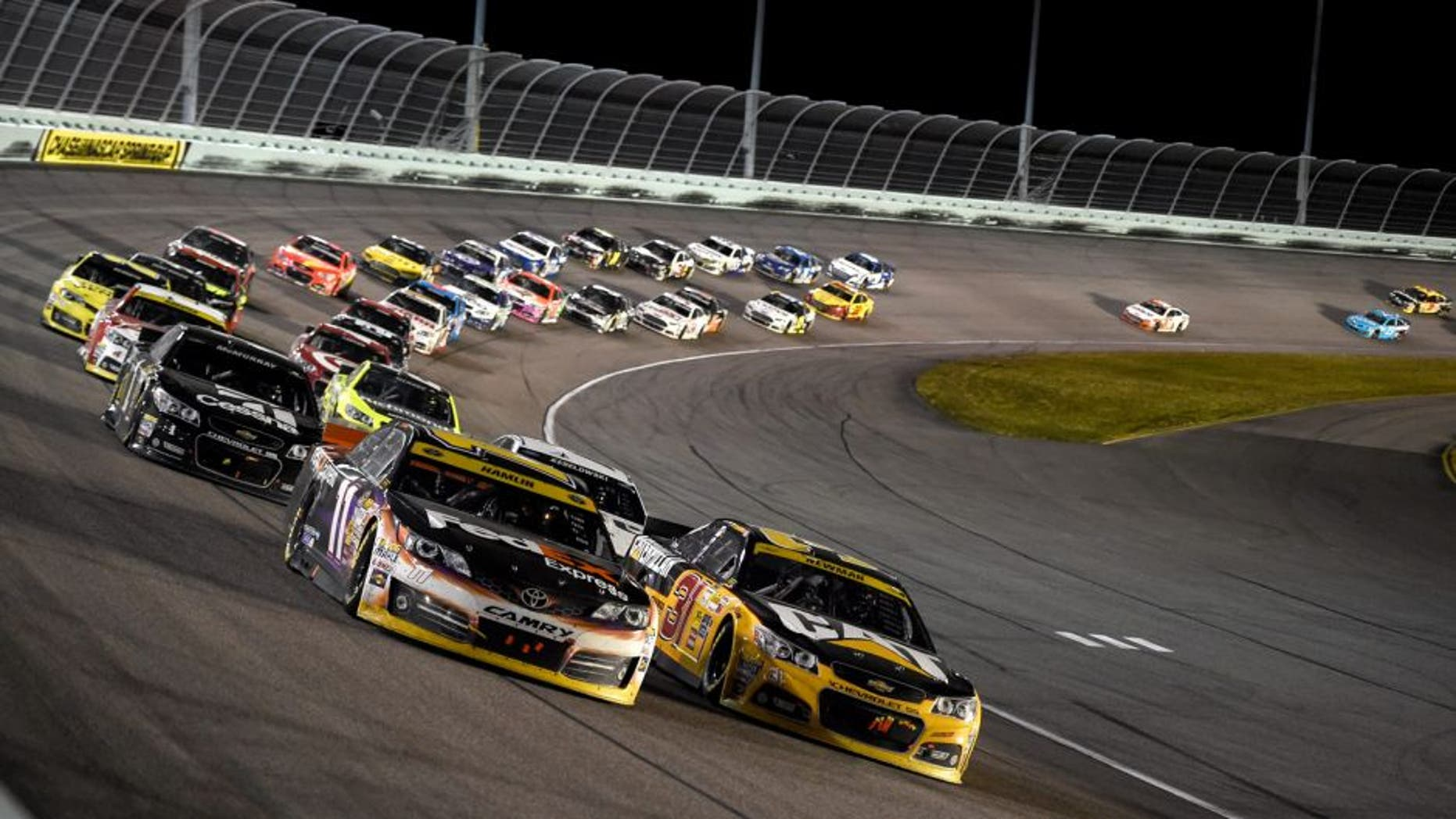 HOMESTEAD, FL - NOVEMBER 16: Denny Hamlin, driver of the #11 FedEx Express Toyota, races with Ryan Newman, driver of the #31 Caterpillar Chevrolet, during the NASCAR Sprint Cup Series Ford EcoBoost 400 at Homestead-Miami Speedway on November 16, 2014 in Homestead, Florida.