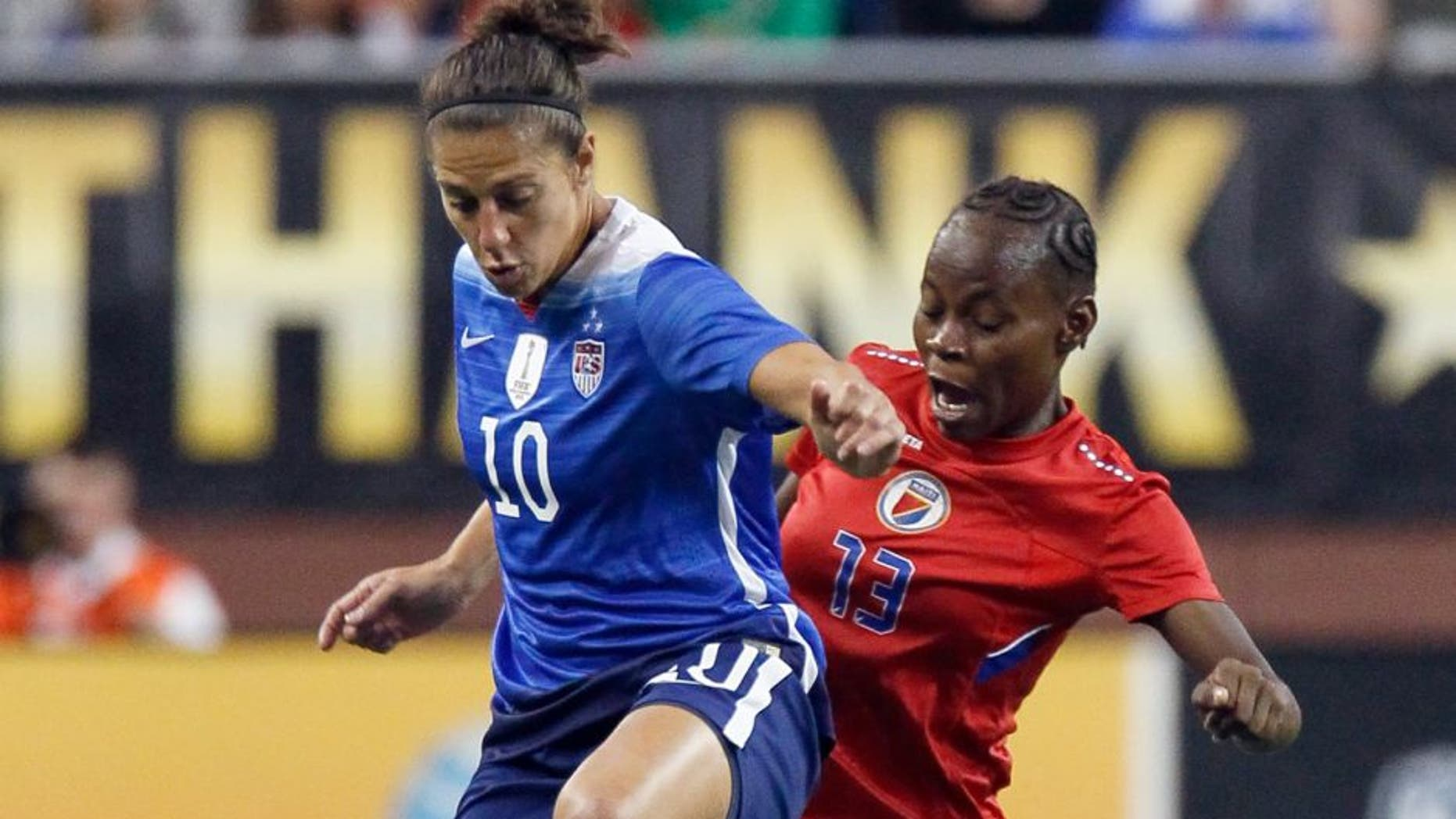 DETROIT, MI - SEPTEMBER 17: Carli Lloyd #10 of the United States tries to keep the ball away from Zila Lafleur #13 of Haiti during the first half of the U.S. Women's 2015 World Cup victory tour match at Ford Field on September 17, 2015, in Detroit, Michigan. (Photo by Duane Burleson/Getty Images)