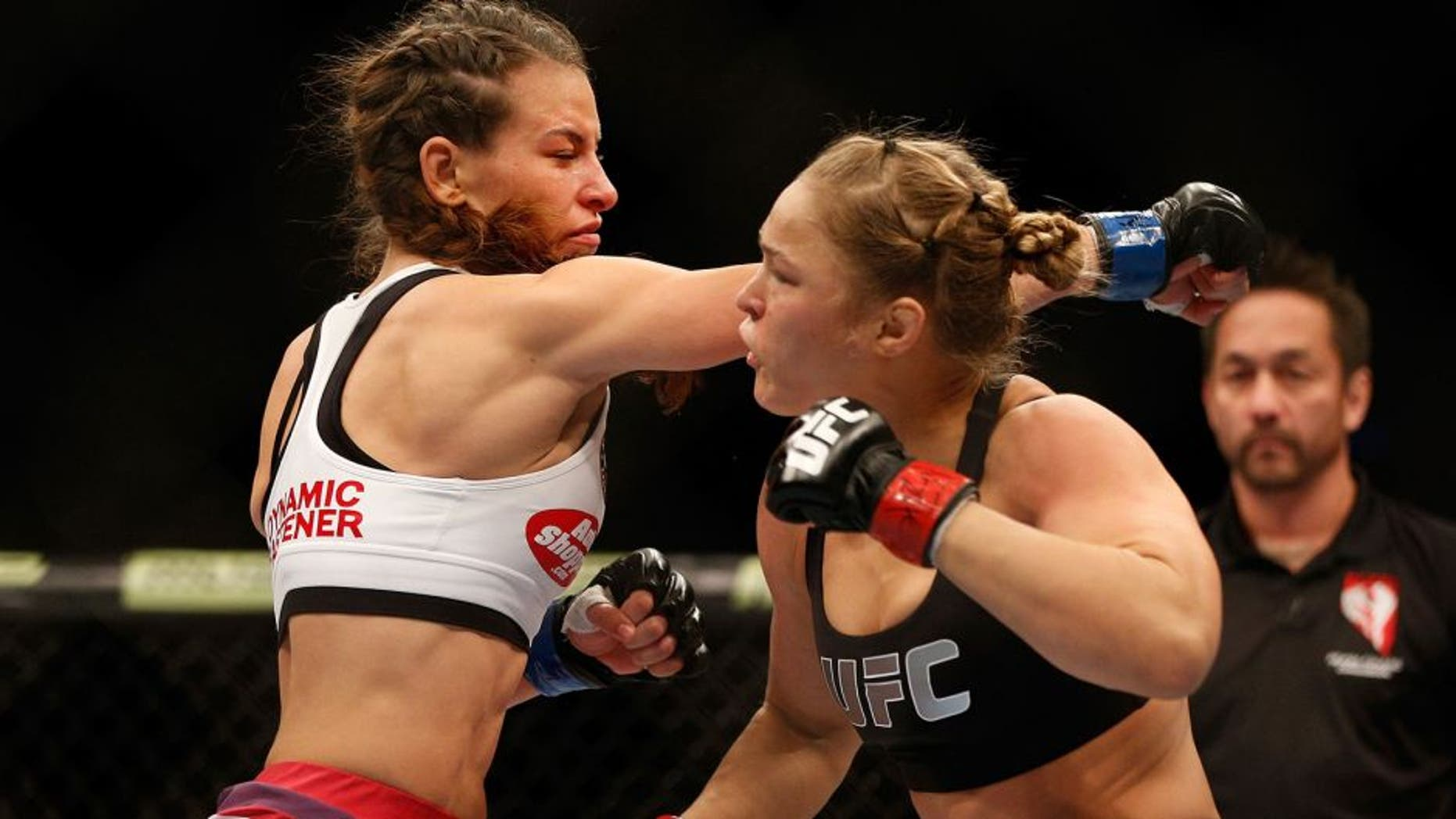 LAS VEGAS, NV - DECEMBER 28: (L-R) Miesha Tate punches Ronda Rousey in their UFC women's bantamweight championship bout during the UFC 168 event at the MGM Grand Garden Arena on December 28, 2013 in Las Vegas, Nevada. (Photo by Josh Hedges/Zuffa LLC/Zuffa LLC via Getty Images) *** Local Caption *** Ronda Rousey; Miesha Tate