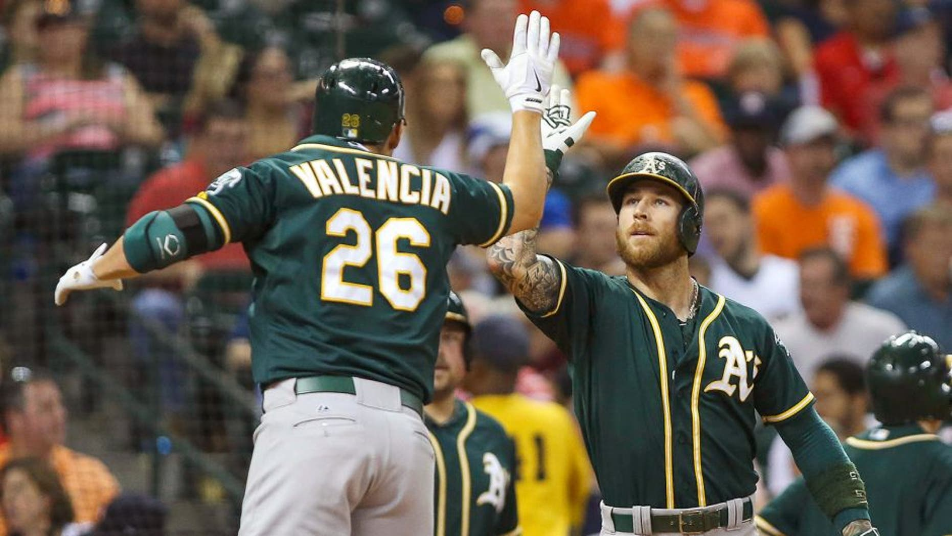Sep 18, 2015; Houston, TX, USA; Oakland Athletics third baseman Danny Valencia (26) celebrates with second baseman Brett Lawrie (15) after hitting a home run during the fourth inning against the Houston Astros at Minute Maid Park. Mandatory Credit: Troy Taormina-USA TODAY Sports