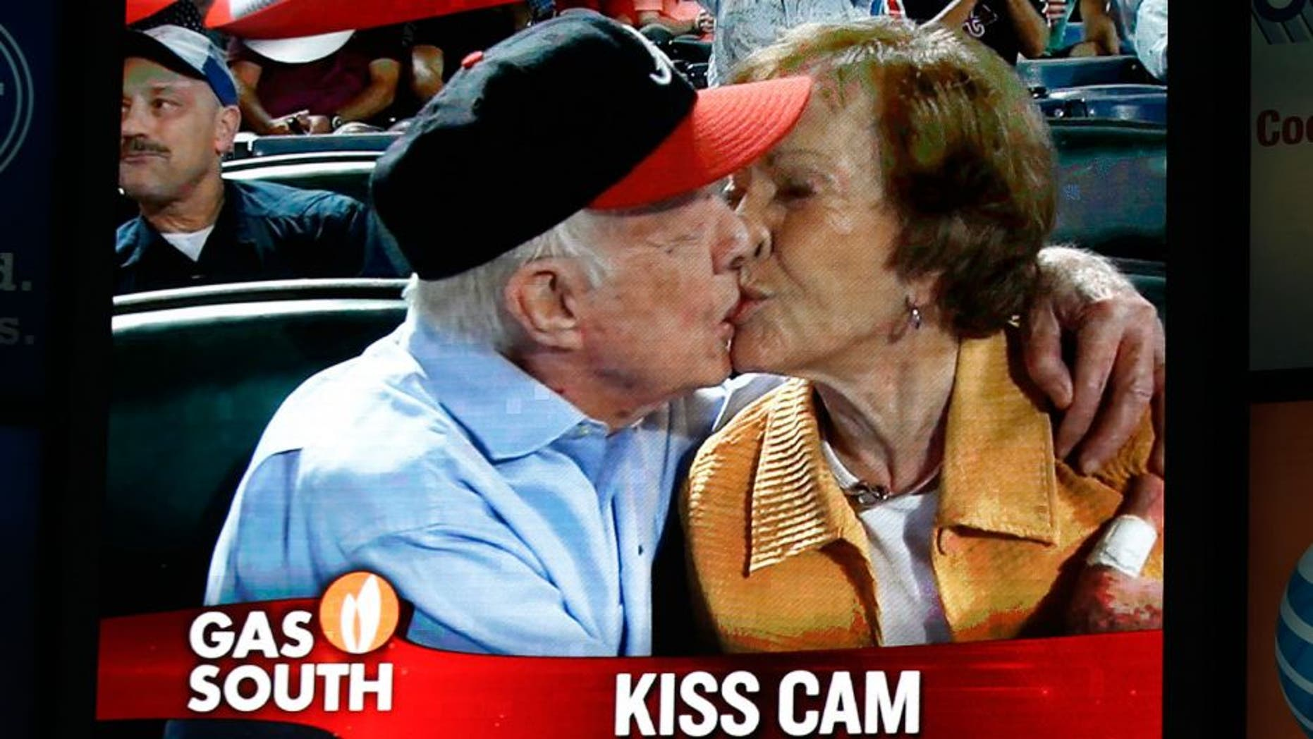 """Former President Jimmy Carter kisses his wife,Rosalynn, on the """"Kiss Cam"""" during a baseball game between the Atlanta Braves and the Toronto Blue Jays on Thursday, Sept. 17, 2015, in Atlanta. Carter recently announced he has cancer. (AP Photo/John Bazemore)"""