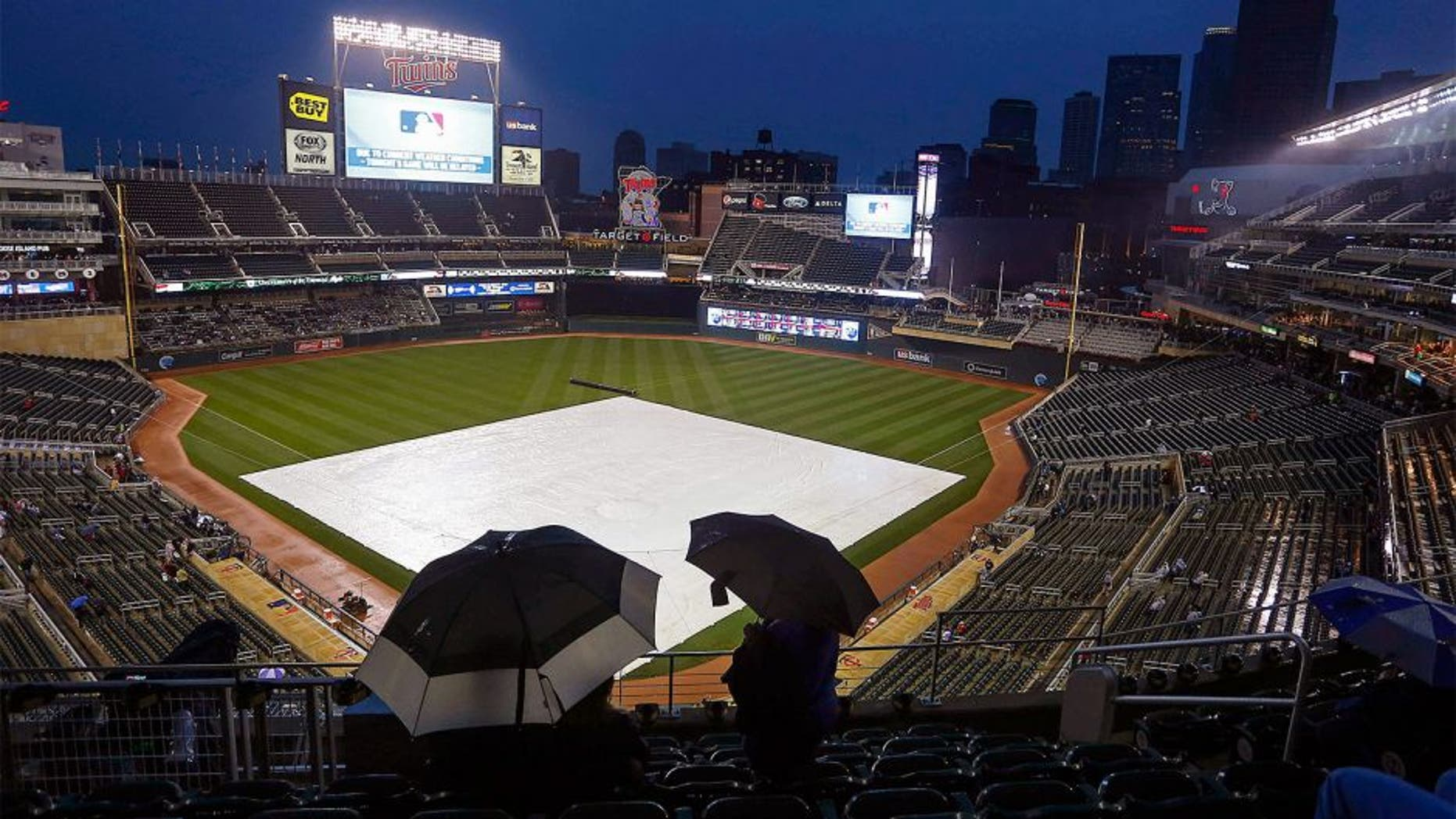 Sep 18, 2015; Minneapolis, MN, USA; Fans hide under umbrellas as rain delays the game between the Los Angeles Angels and the Minnesota Twins at Target Field. Mandatory Credit: Bruce Kluckhohn-USA TODAY Sports
