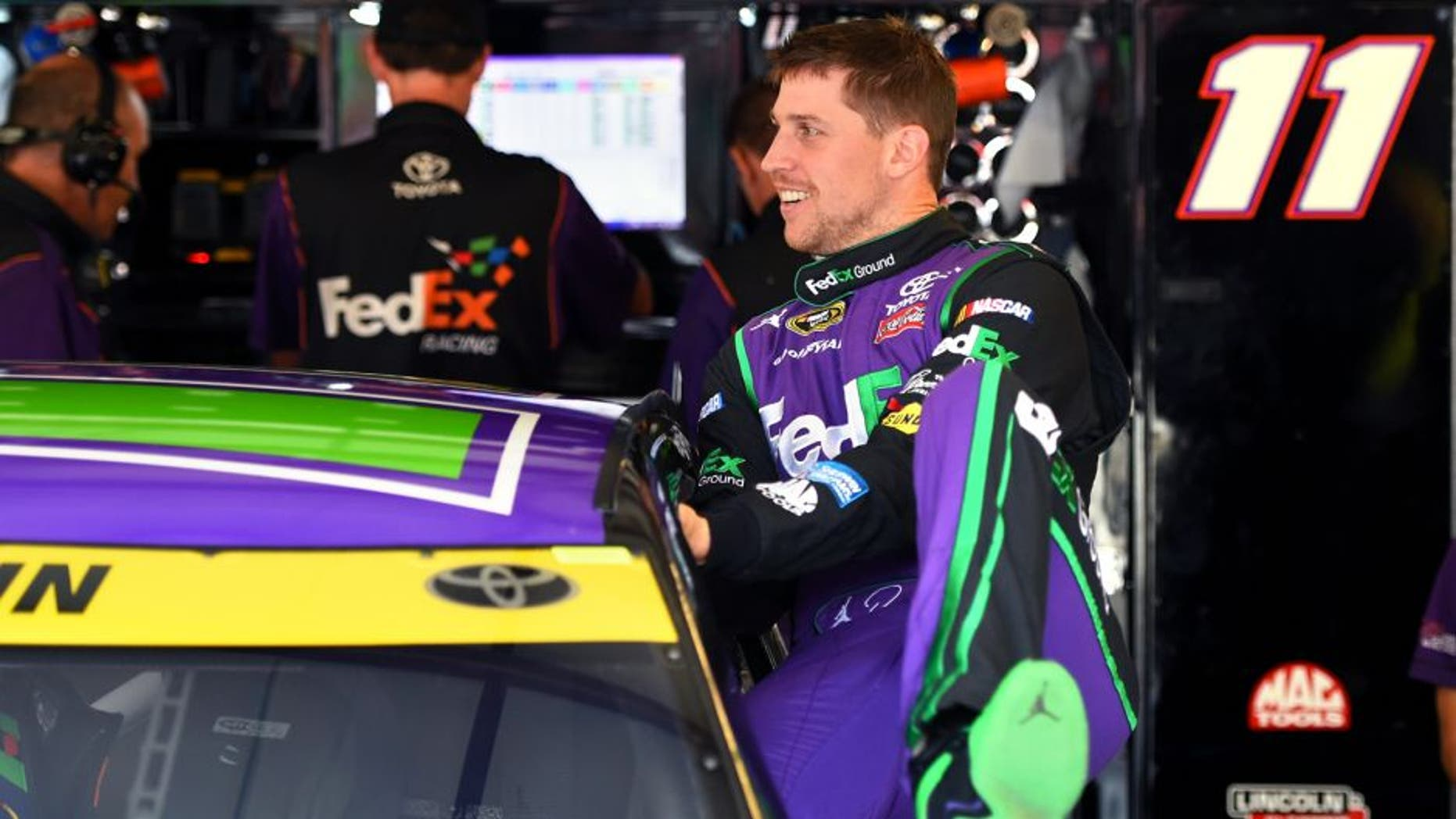 JOLIET, IL - SEPTEMBER 18: Denny Hamlin, driver of the #11 FedEx Ground Toyota, climbs into his car before practice for the NASCAR Sprint Cup Series myAFibRisk.com 400 at Chicagoland Speedway on September 18, 2015 in Joliet, Illinois. (Photo by Josh Hedges/Getty Images)
