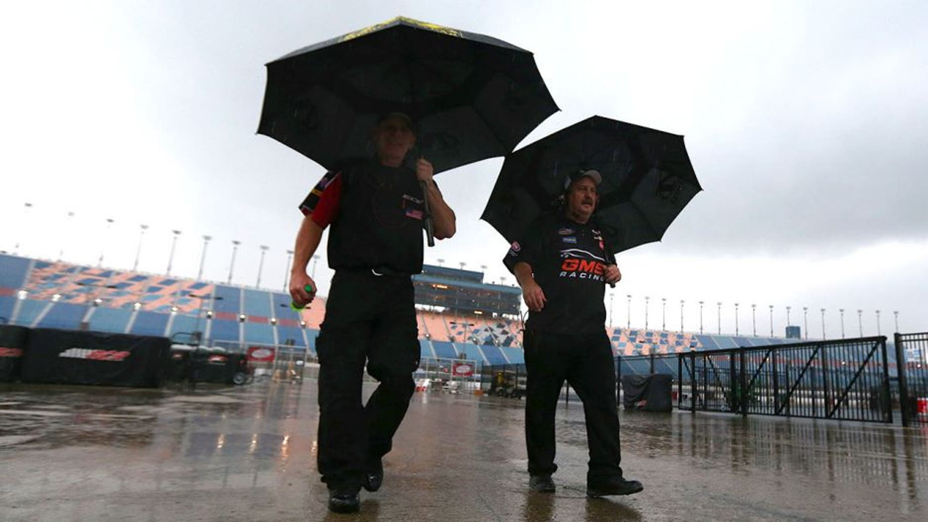 JOLIET, IL - SEPTEMBER 18: Crew members walk off pit road under heavy rain during qualifying for the NASCAR Camping World Truck Series American Ethanol E15 225 at Chicagoland Speedway on September 18, 2015 in Joliet, Illinois. (Photo by Sarah Crabill/NASCAR via Getty Images)