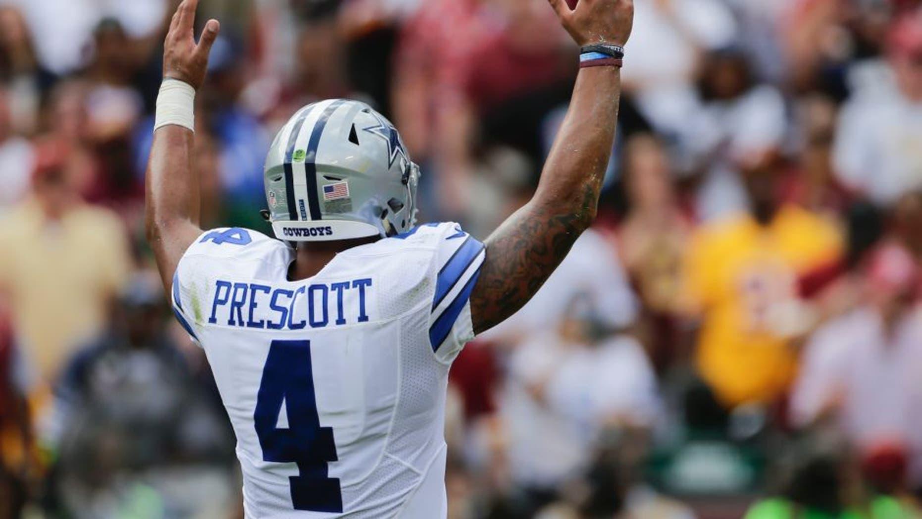 Dallas Cowboys quarterback Dak Prescott (4) celebrates running back Ezekiel Elliott's touchdown during the first half of an NFL football game against the Washington Redskins in Landover, Md., Sunday, Sept. 18, 2016. (AP Photo/Mark Tenally)