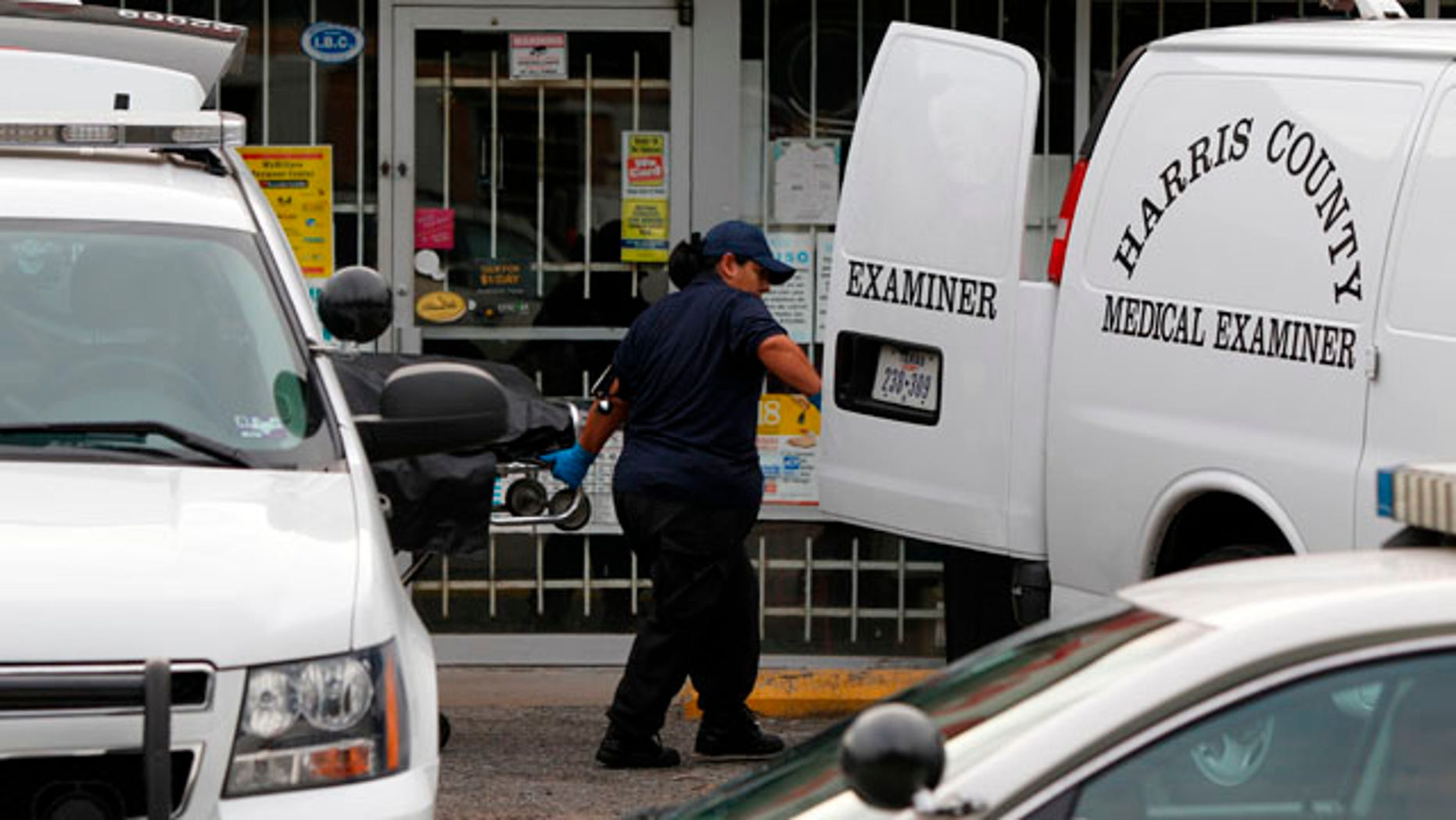 Sept. 19: Harris County Medical Examiner personnel remove one of three bodies from the scene.