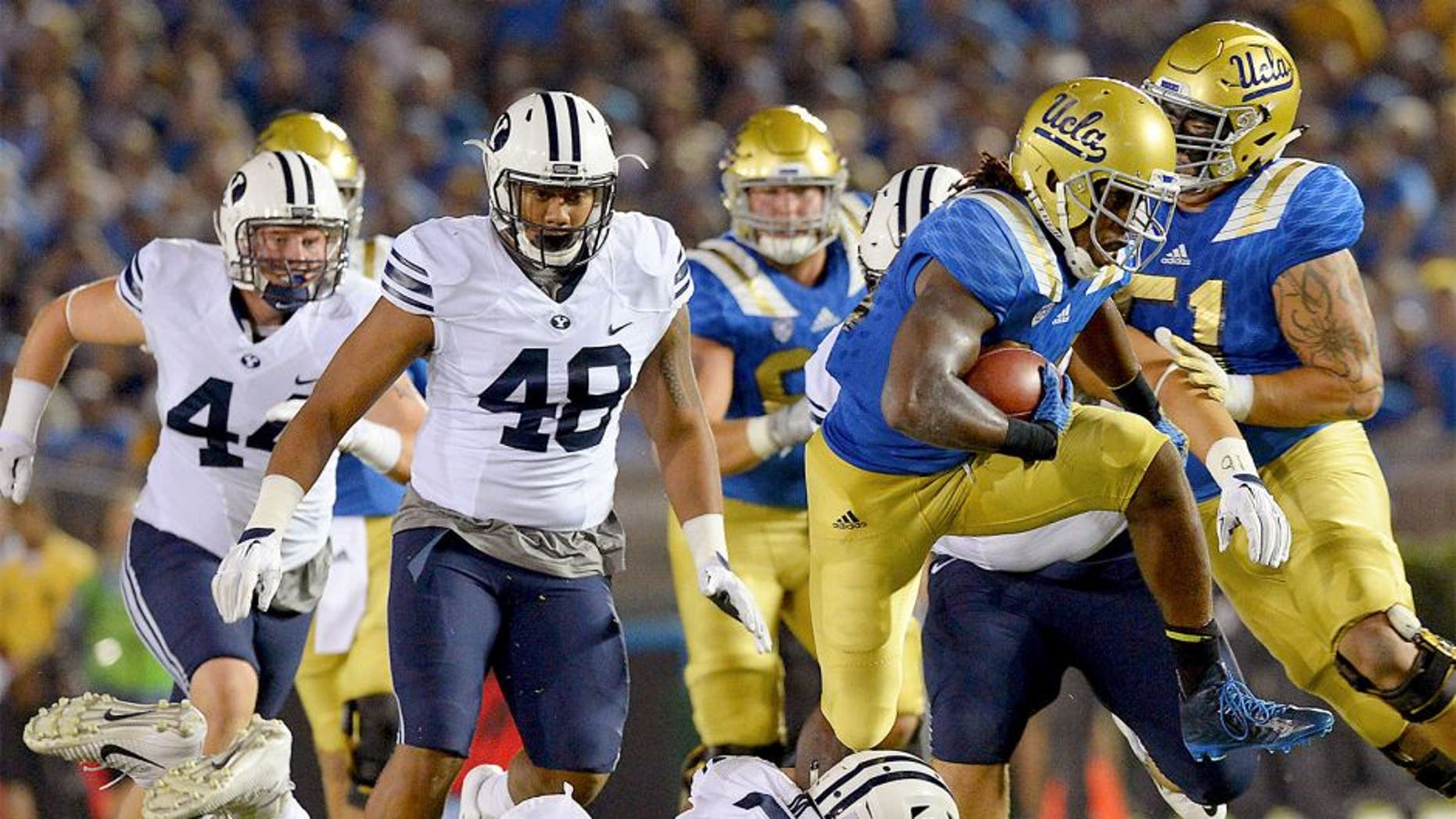 Sep 19, 2015; Pasadena, CA, USA; UCLA Bruins running back Paul Perkins (24) is stopped by Brigham Young Cougars linebacker Manoa Pikula (22) after a gain in the second quarter of the game at the Rose Bowl. Mandatory Credit: Jayne Kamin-Oncea-USA TODAY Sports