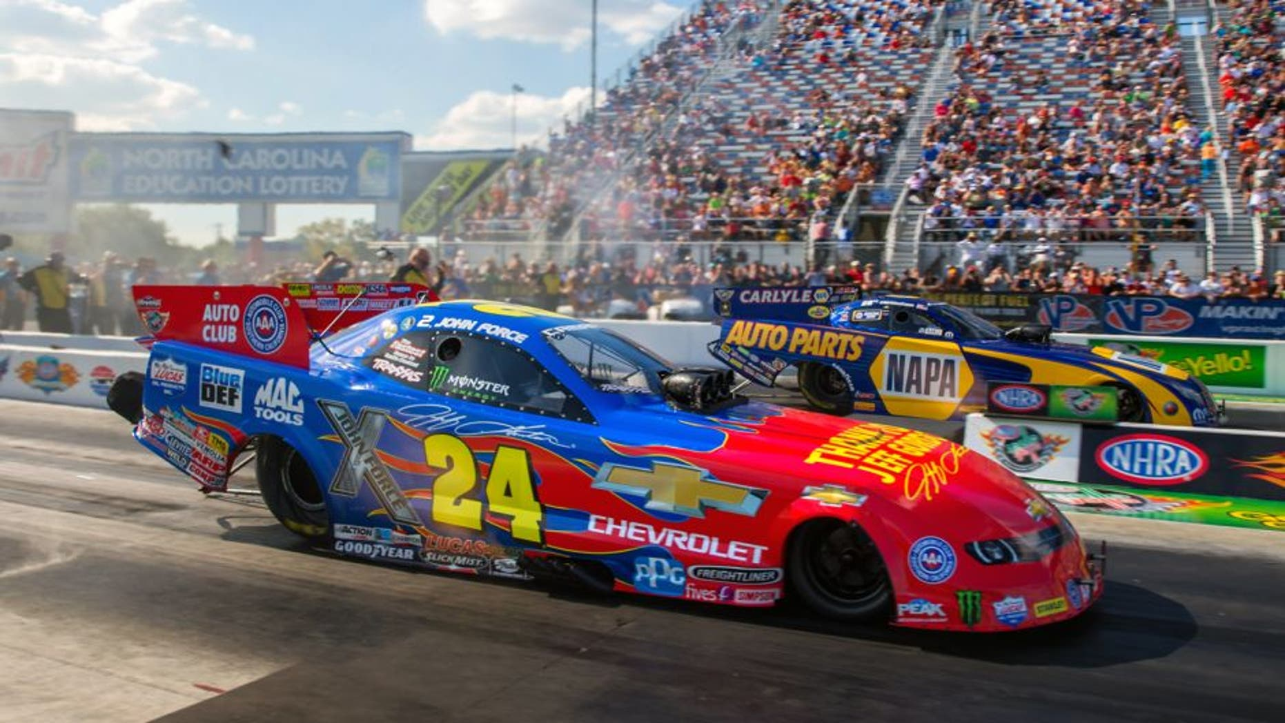 Sep 18, 2015; Concord, NC, USA; NHRA funny car driver John Force (near) in his special paint scheme honoring retiring NASCAR driver Jeff Gordon as he races alongside Ron Capps during qualifying for the Carolina Nationals at zMax Dragway. Mandatory Credit: Mark J. Rebilas-USA TODAY Sports