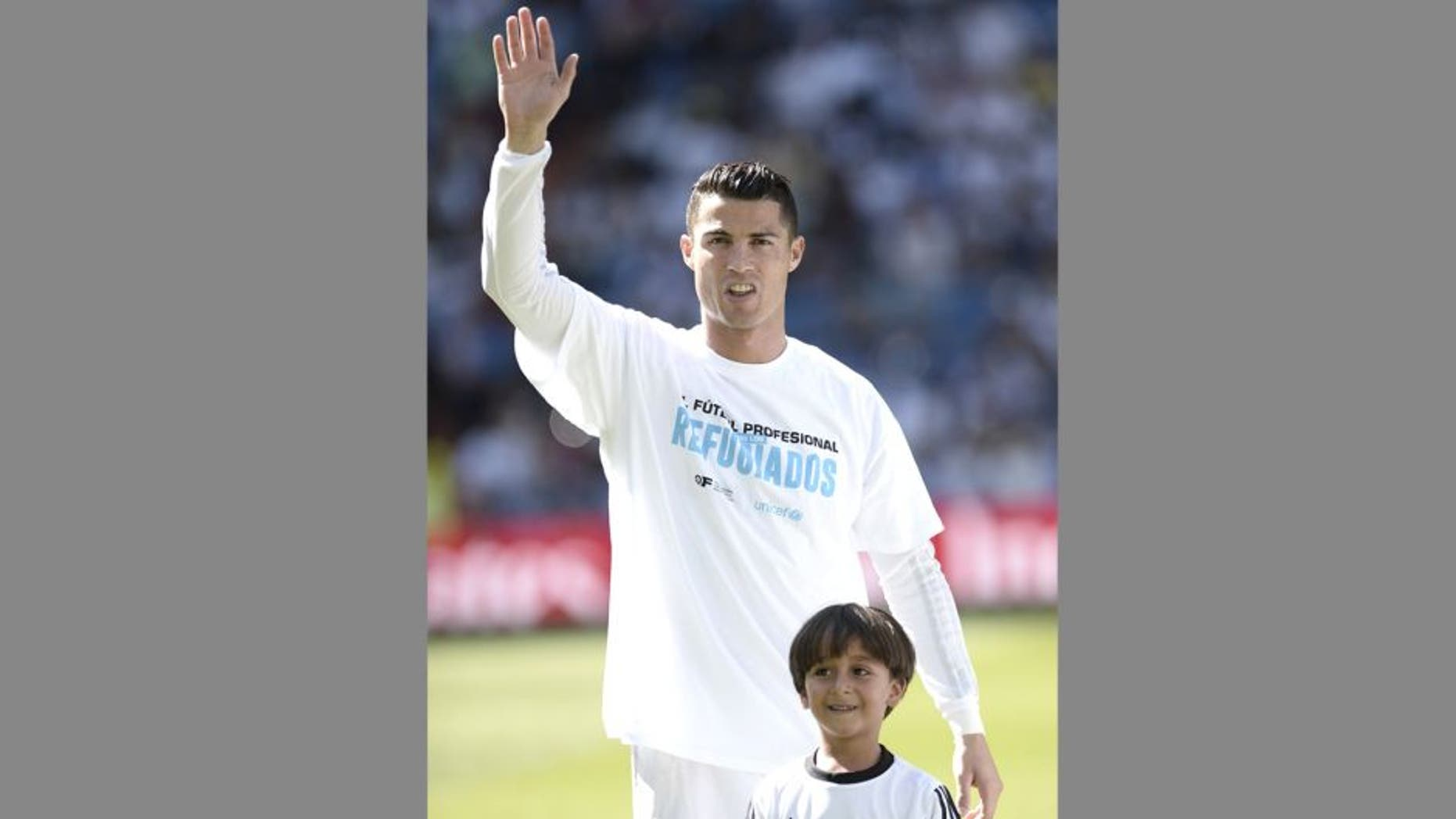 MADRID, SPAIN - SEPTEMBER 19: Zaid (R), son of Osama Abdul Mohsen (not seen), the Syrian refugee who had tripped over by a Hungarian journalist, pose with Cristiano Ronaldo (L) of Real Madrid before La Liga football match between Real Madrid CF vs Granada FC as the guests of Real Madrid CF at the Santiago Bernabeu stadium in Madrid on September 19, 2015. (Photo by Burak Akbulut/Anadolu Agency/Getty Images)