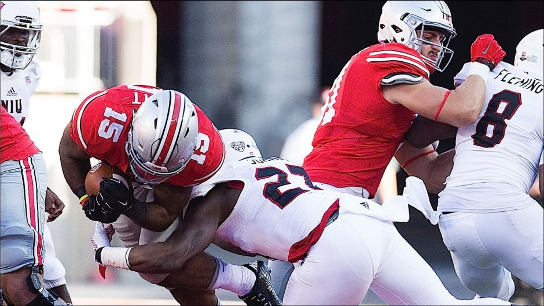 Sep 19, 2015; Columbus, OH, USA; Ohio State Buckeyes running back Ezekiel Elliott (15) is knocked off his feet by Northern Illinois Huskies safety Jawuan Johnson (27) at Ohio Stadium. Ohio State won the game 20-13. Mandatory Credit: Greg Bartram-USA TODAY Sports