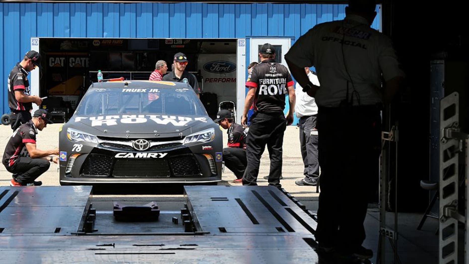 BROOKLYN, MI - JUNE 10: NASCAR officials inspect the #78 Furniture Row Toyota driven by Martin Truex Jr. (not pictured) prior to qualifying for the NASCAR Sprint Cup Series FireKeepers Casino 400 at Michigan International Speedway on June 10, 2016 in Brooklyn, Michigan. (Photo by Jerry Markland/Getty Images )