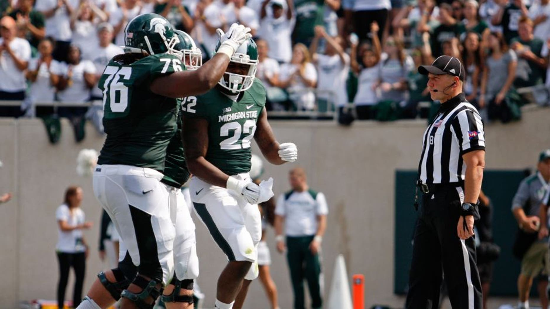 Sep 20, 2014; East Lansing, MI, USA; Michigan State Spartans running back Delton Williams (22) celebrates after a touchdown during the second quarter against the Eastern Michigan Eagles at Spartan Stadium. Mandatory Credit: Raj Mehta-USA TODAY Sports