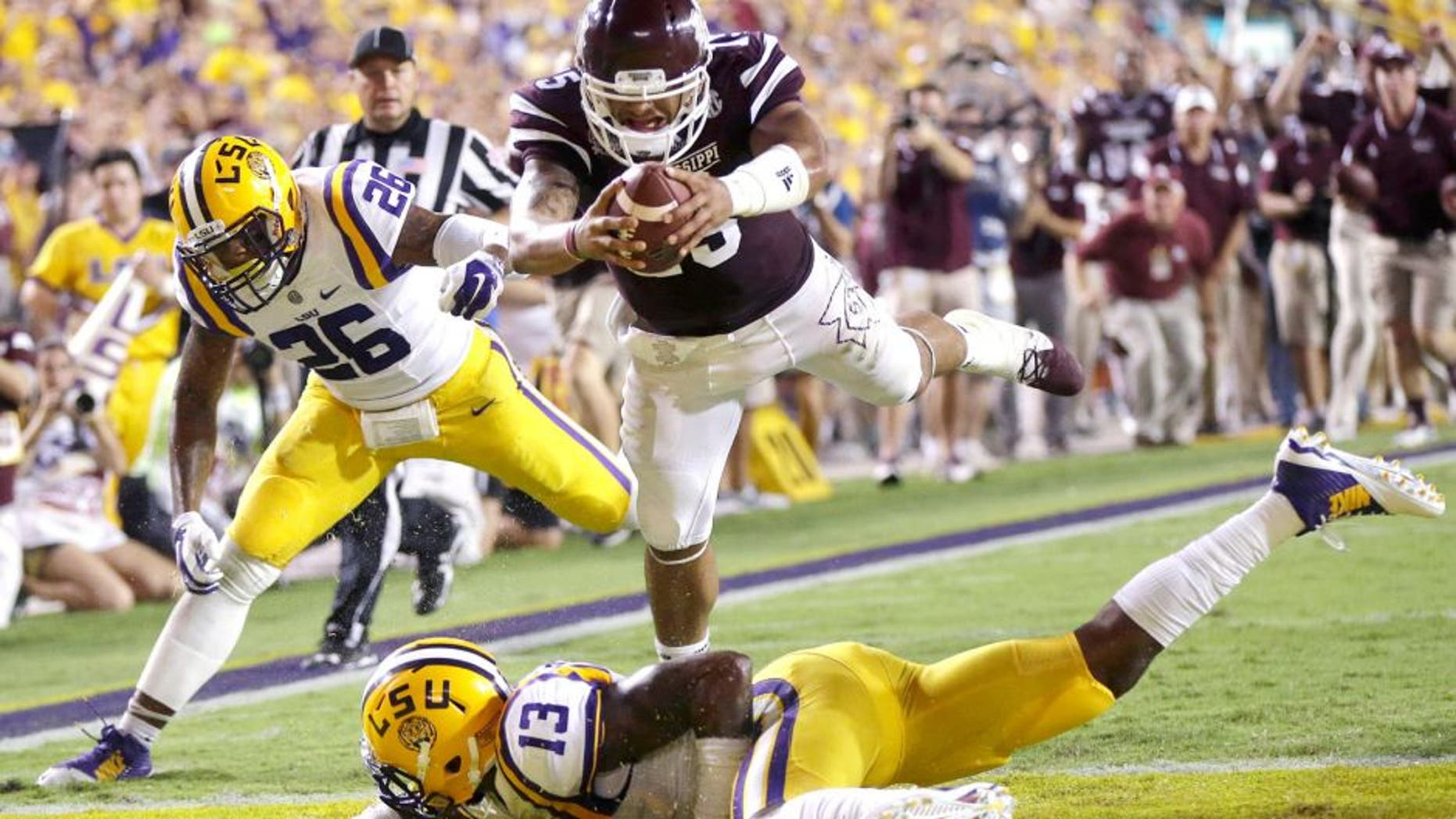 Mississippi State quarterback Dak Prescott (15) dives into the end zone over LSU cornerback Dwayne Thomas (13) and safety Ronald Martin (26) on a 56 yard touchdown run in the second half of an NCAA college football game in Baton Rouge, La., Saturday, Sept. 20, 2014. (AP Photo/Gerald Herbert)