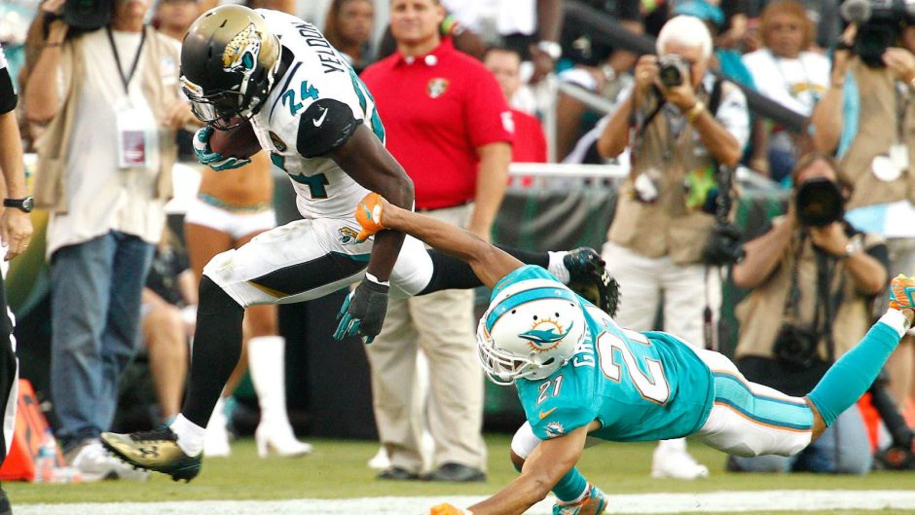 Sep 20, 2015; Jacksonville, FL, USA; Jacksonville Jaguars running back T.J. Yeldon (24) runs past Miami Dolphins cornerback Brent Grimes (21) during the second half of an NFL Football game at EverBank Field. The Jacksonville Jaguars won 23-20. Mandatory Credit: Reinhold Matay-USA TODAY Sports