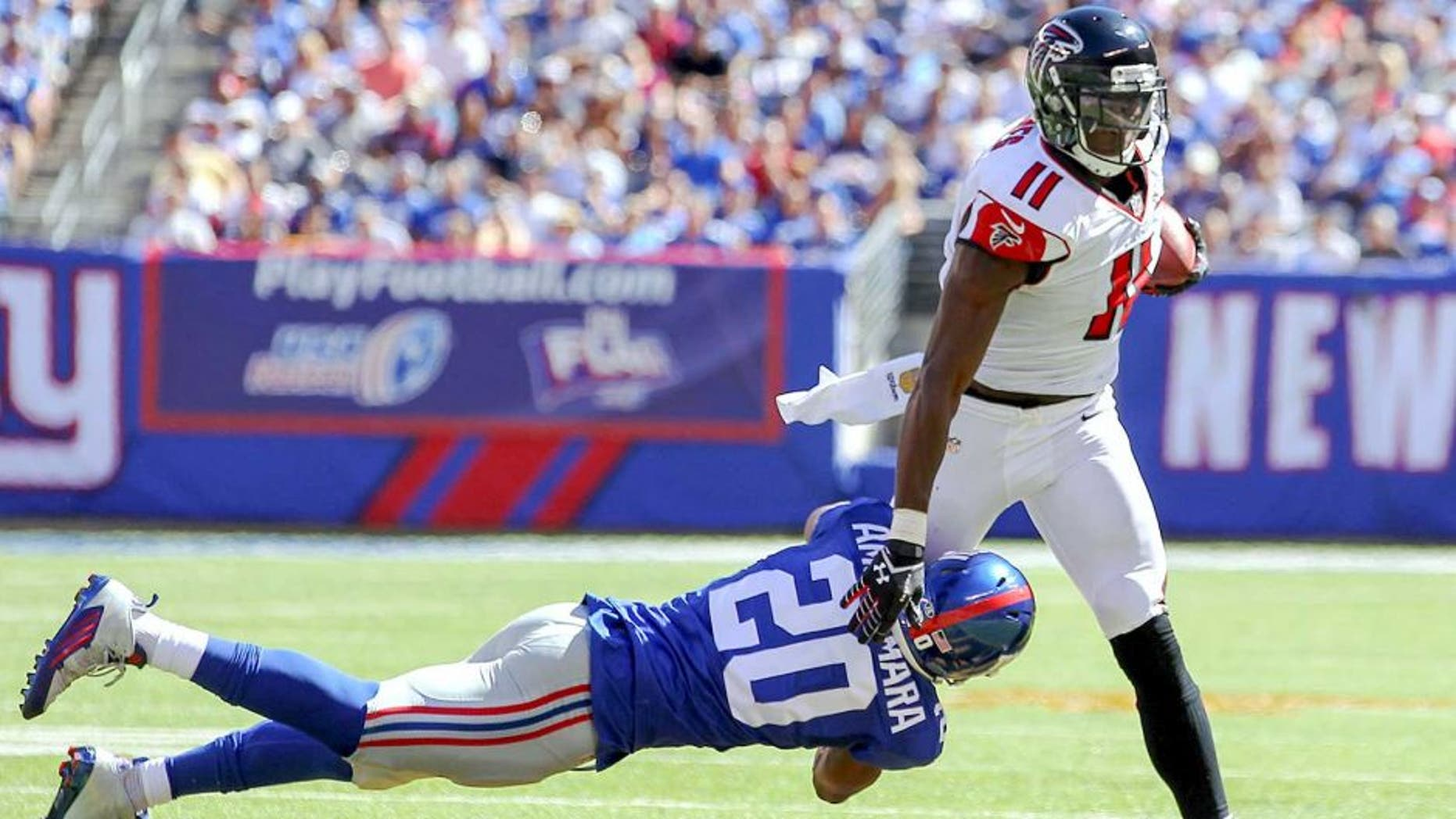 Sep 20, 2015; East Rutherford, NJ, USA; Atlanta Falcons wide receiver Julio Jones (11) runs with the ball while trying to avoid a tackle by New York Giants cornerback Prince Amukamara (20) during the first half at MetLife Stadium. Mandatory Credit: Ed Mulholland-USA TODAY Sports
