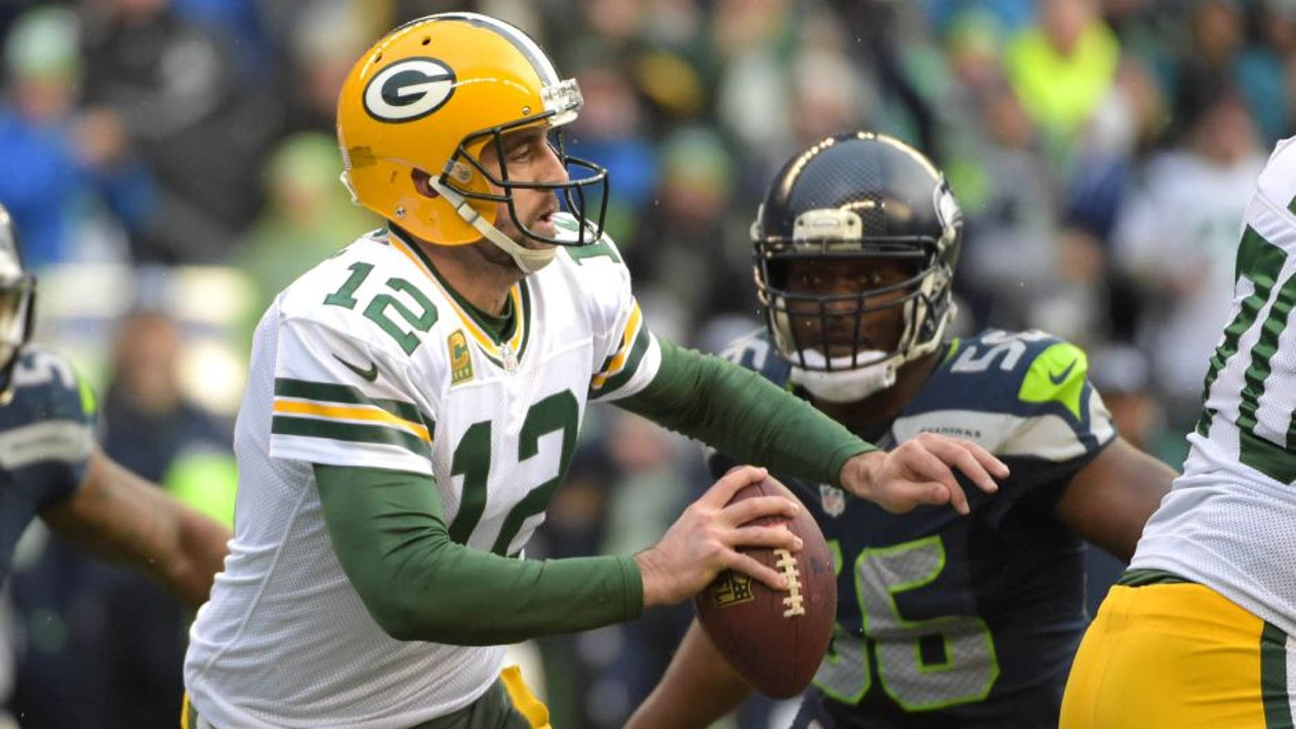 Jan 18, 2015; Seattle, WA, USA; Green Bay Packers quarterback Aaron Rodgers (12) looks to throw the ball against the Seattle Seahawks during the fourth quarter in the NFC Championship Game at CenturyLink Field. Mandatory Credit: Kirby Lee-USA TODAY Sports