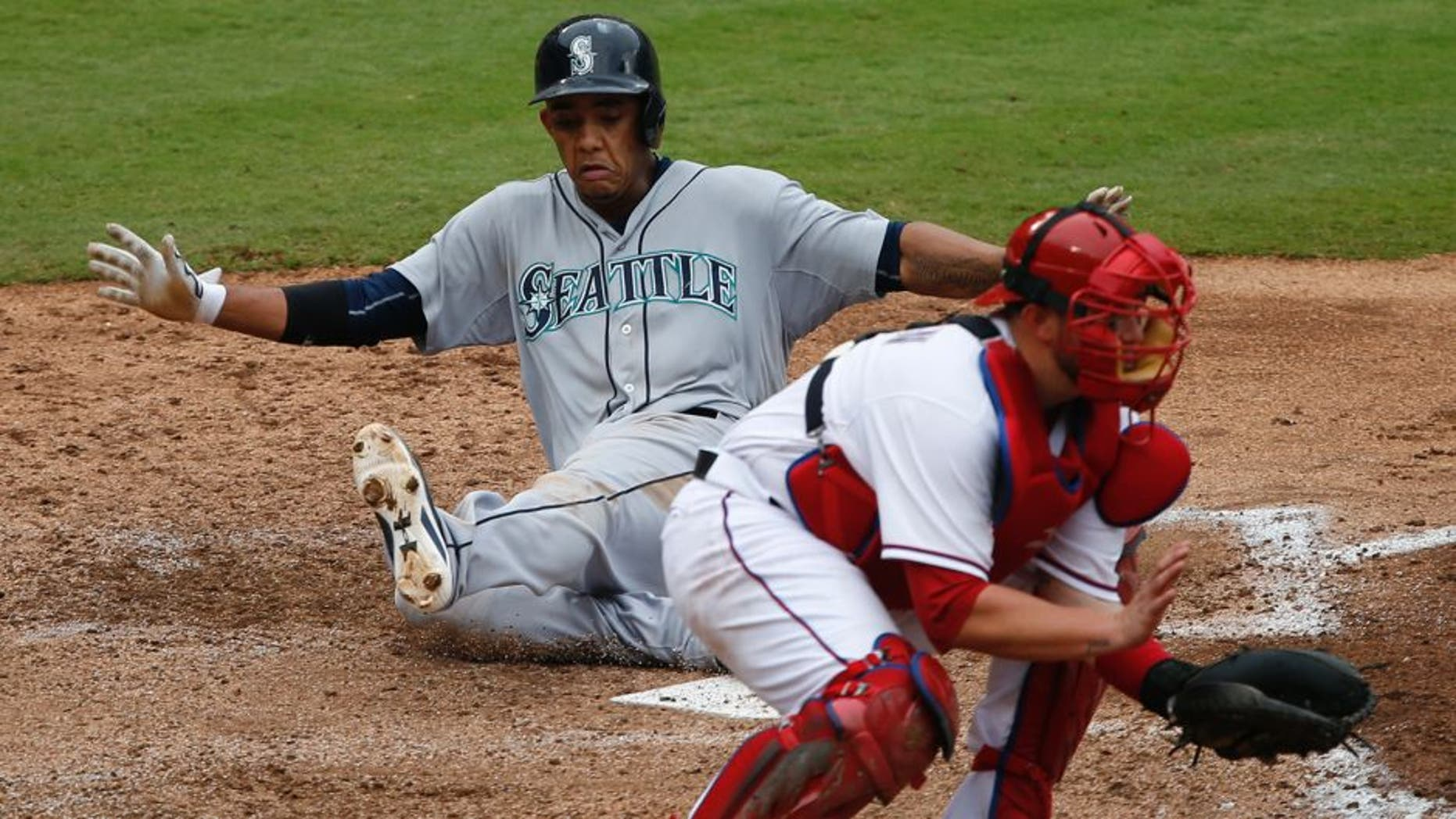 Sep 20, 2015; Arlington, TX, USA; Seattle Mariners shortstop Ketel Marte (4) slides to score a run ahead of the throw to Texas Rangers catcher Bobby Wilson (8) during the fifth inning of a baseball game at Globe Life Park in Arlington. Mandatory Credit: Jim Cowsert-USA TODAY Sports