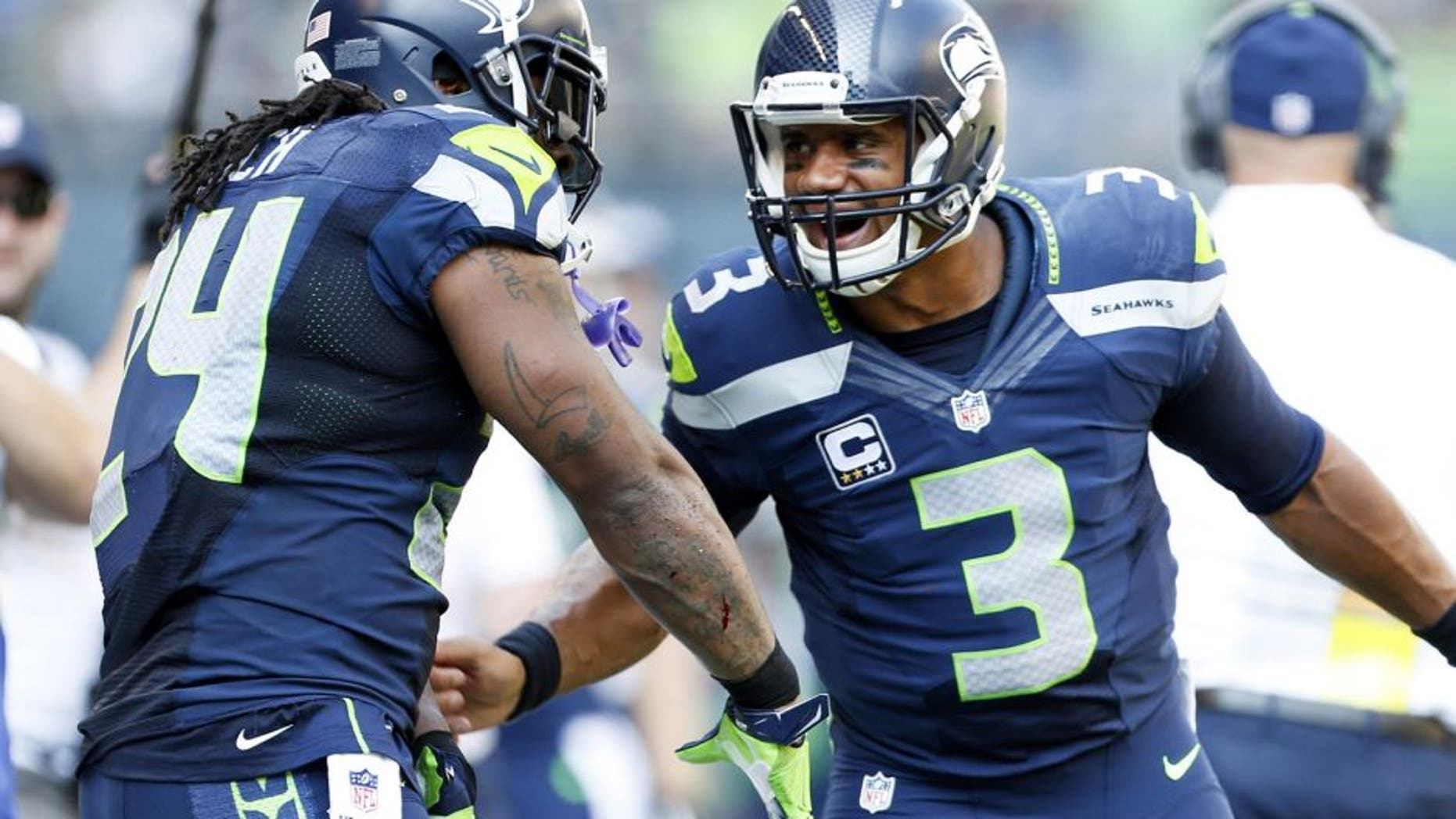Sep 21, 2014; Seattle, WA, USA; Seattle Seahawks quarterback Russell Wilson (3) celebrates with Seattle Seahawks running back Marshawn Lynch (24) after a touchdown pass during the second quarter against the Denver Broncos at CenturyLink Field. Mandatory Credit: Joe Nicholson-USA TODAY Sports