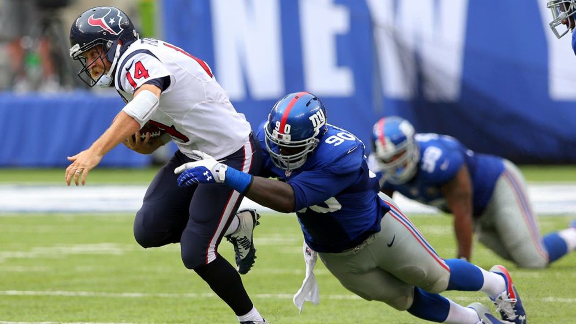 Sep 21, 2014; East Rutherford, NJ, USA; Houston Texans quarterback Ryan Fitzpatrick (14) is brought down by New York Giants defensive end Jason Pierre-Paul (90) during the fourth quarter at MetLife Stadium. Mandatory Credit: Brad Penner-USA TODAY Sports