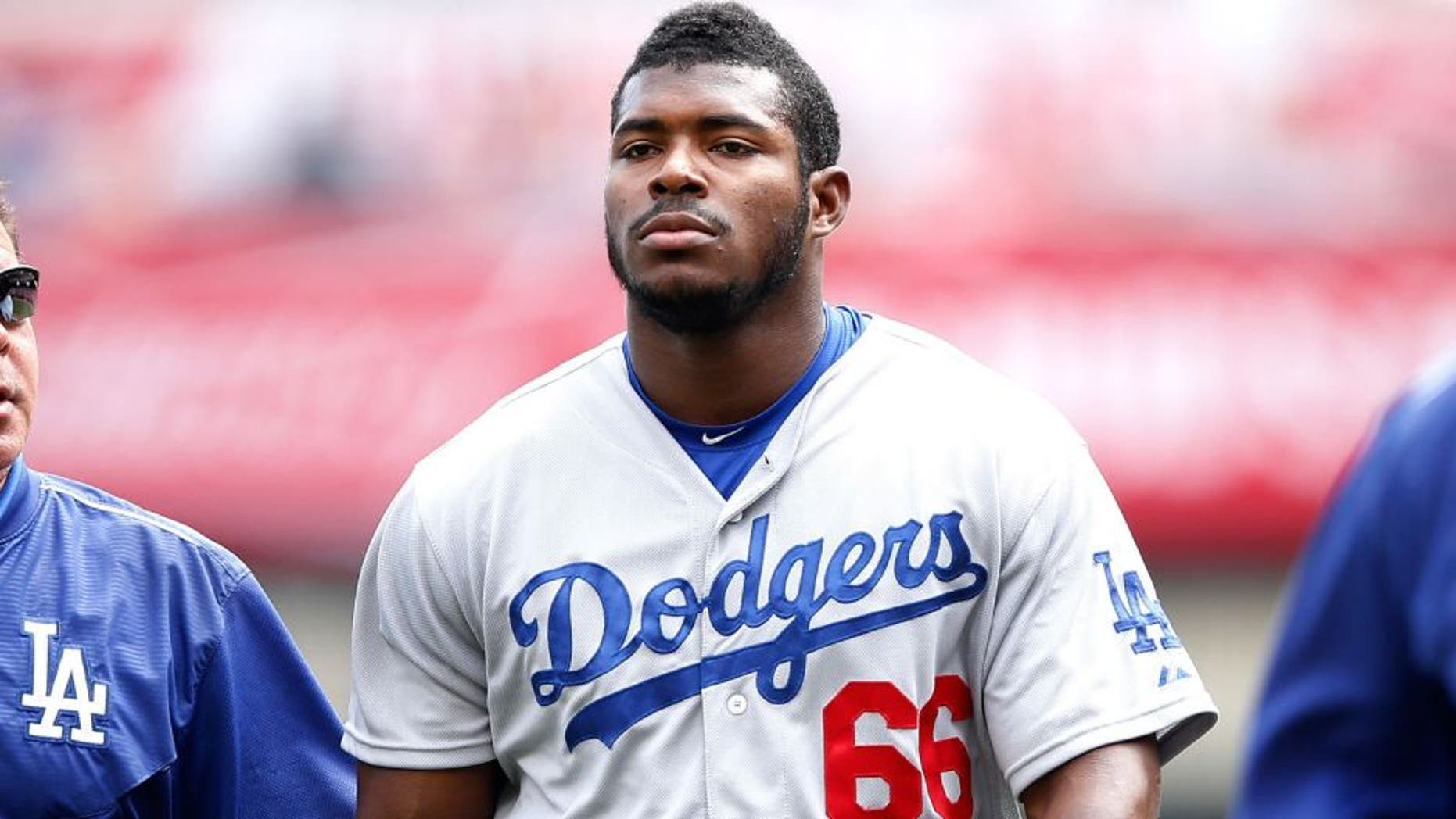 CINCINNATI, OH - AUGUST 27: Yasiel Puig #66 of the Los Angeles Dodgers walks off the field with director of medical services Stan Conte after suffering an injury during the game against the Cincinnati Reds at Great American Ball Park on August 27, 2015 in Cincinnati, Ohio. The Dodgers defeated the Reds 1-0. (Photo by Joe Robbins/Getty Images)