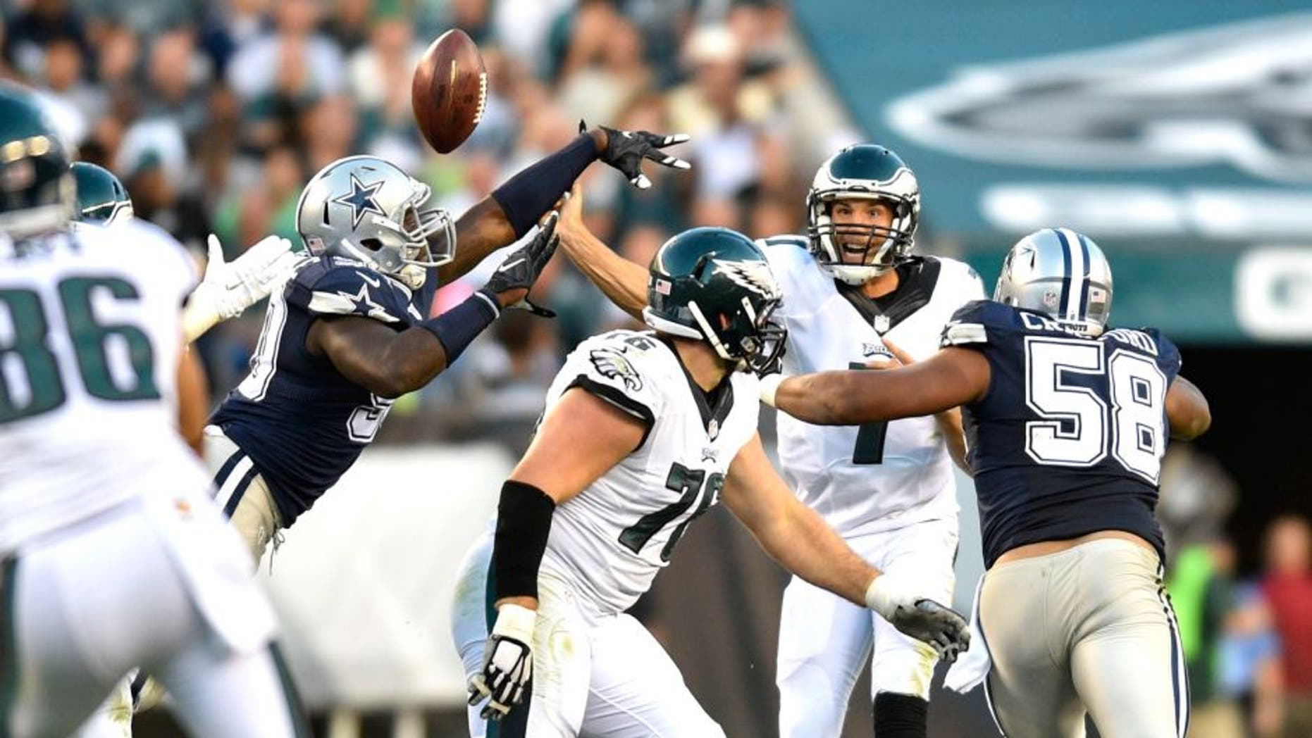 Sep 20, 2015; Philadelphia, PA, USA; Philadelphia Eagles quarterback Sam Bradford (7) has the ball tipped by Dallas Cowboys defensive lineman DeMarcus Lawrence (left) as defensive tackle Jack Crawford (58) defends in the third quarter at Lincoln Financial Field. Mandatory Credit: James Lang-USA TODAY Sports