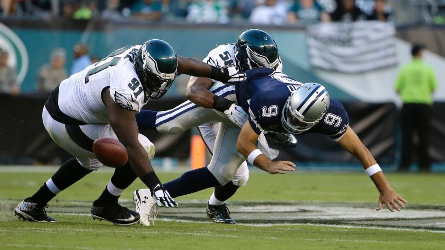 Dallas Cowboys' Tony Romo (9) fumbles the football against Philadelphia Eagles' Fletcher Cox (91) and Jordan Hicks (58) during the second half of an NFL football game, Sunday, Sept. 20, 2015, in Philadelphia. (AP Photo/Matt Rourke)
