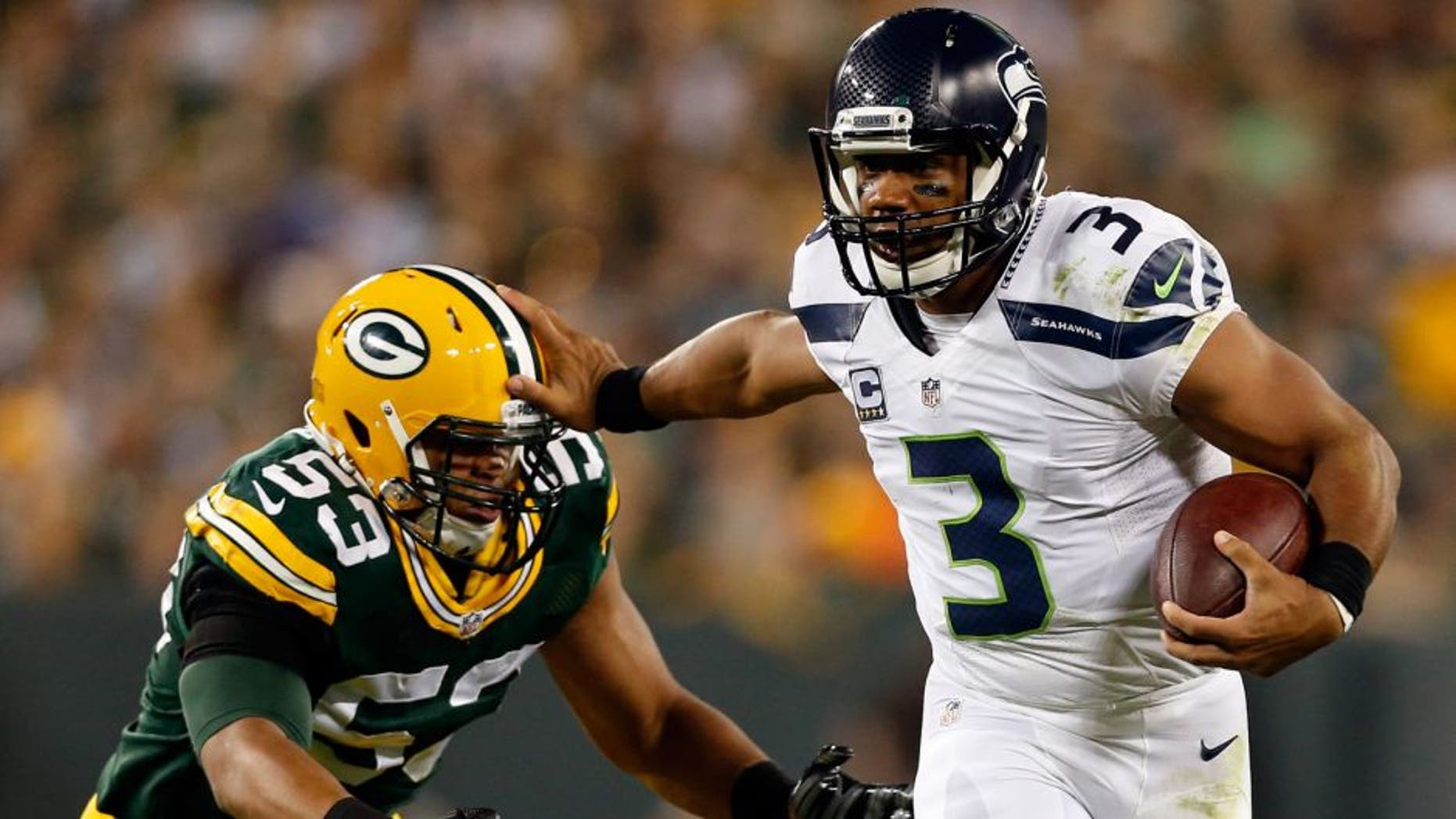 GREEN BAY, WI - SEPTEMBER 20: Russell Wilson #3 of the Seattle Seahawks stiff arms Nick Perry #53 of the Green Bay Packers during the third quarter in their game at Lambeau Field on September 20, 2015 in Green Bay, Wisconsin. (Photo by Christian Petersen/Getty Images)