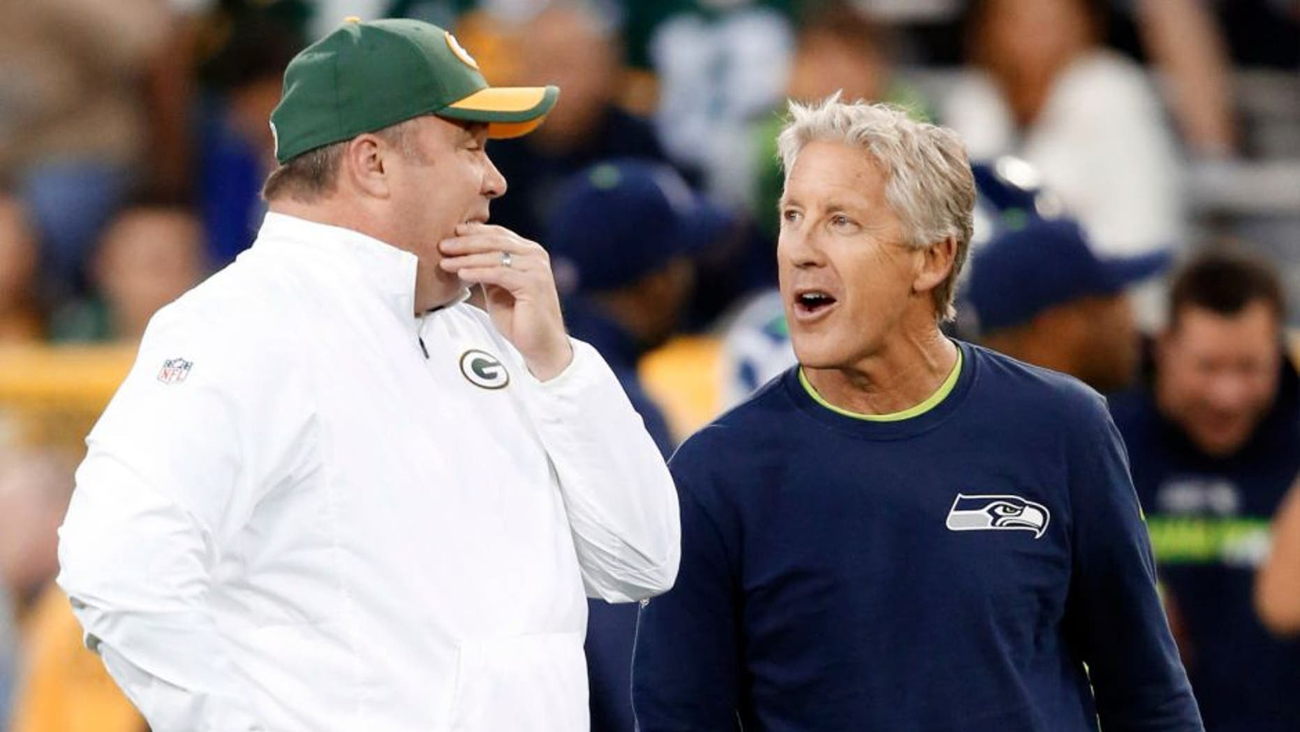 Green Bay Packers head coach Mike McCarthy (left) talks to Seattle Seahawks head coach Pete Carroll before an NFL football game Sunday, Sept. 20, 2015, in Green Bay, Wis.