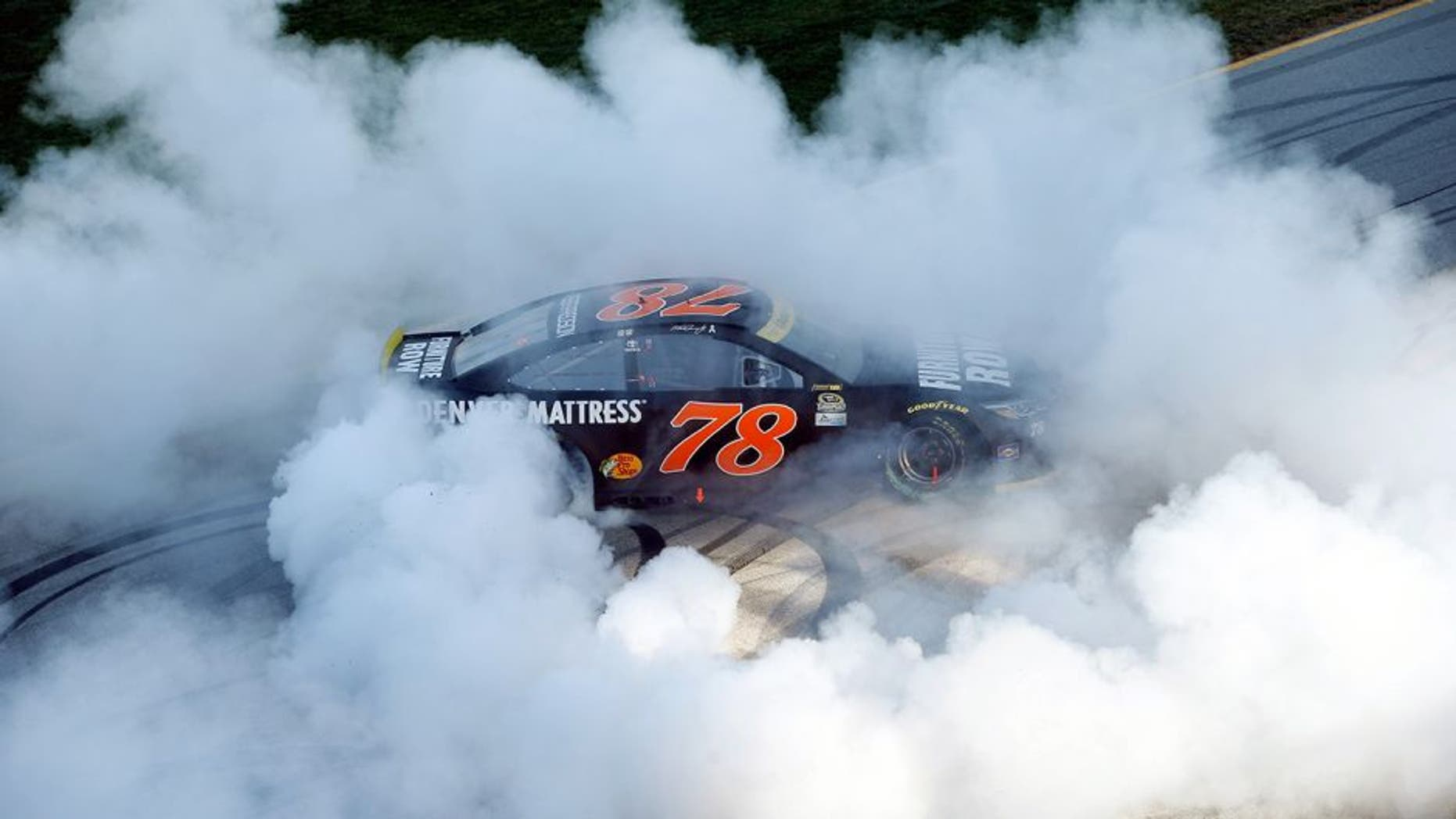 JOLIET, IL - SEPTEMBER 18: Martin Truex Jr, driver of the #78 Furniture Row/Denver Mattress Toyota, celebrates with a burnout after winning the NASCAR Sprint Cup Series Teenage Mutant Ninja Turtles 400 at Chicagoland Speedway on September 18, 2016 in Joliet, Illinois. (Photo by Brian Lawdermilk/NASCAR via Getty Images)