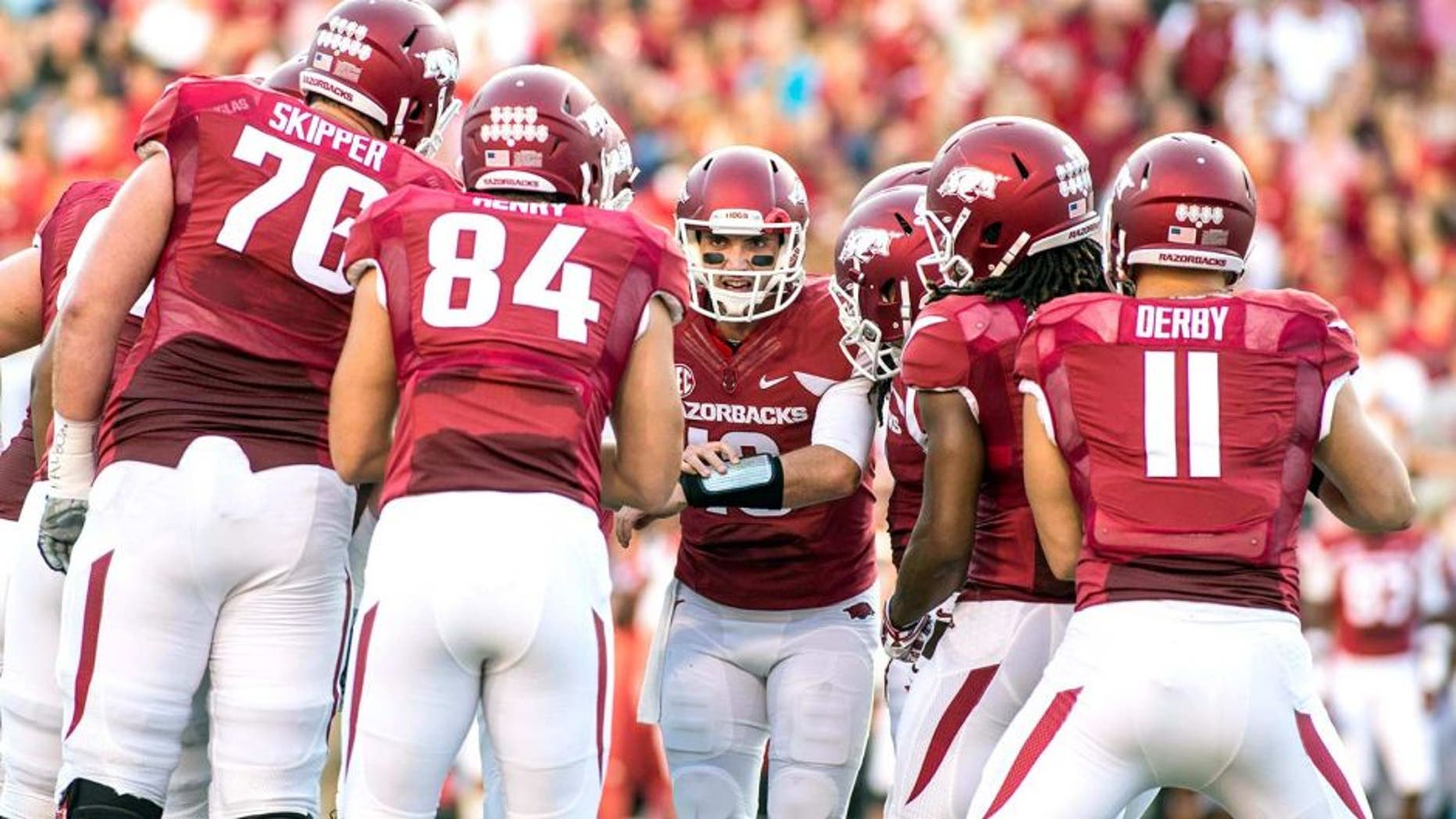 Sep 20, 2014; Fayetteville, AR, USA; Arkansas Razorbacks quarterback Brandon Allen (10, center) calls a play as offensive tackle Dan Skipper (74) tight end Henry Hunter (84) tightened A.J. Derby (11) and other players look on during the first half of a game against Northern Illinois Huskies at Donald W. Reynolds Razorback Stadium. Mandatory Credit: Beth Hall-USA TODAY Sports