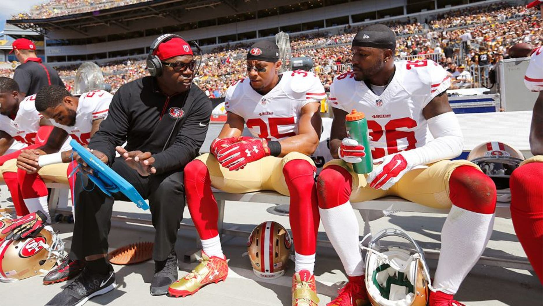 PITTSBURGH, PA - SEPTEMBER 20: Defensive Backs Coach Tim Lewis of the San Francisco 49ers talks with Eric Reid #35 and Tramaine Brock #26 on the sideline during the game against the Pittsburgh Steelers at Heinz Field on September 20, 2015 in Pittsburgh, Pennsylvania. The Steelers defeated the 49ers 43-18. (Photo by Michael Zagaris/San Francisco 49ers/Getty Images)