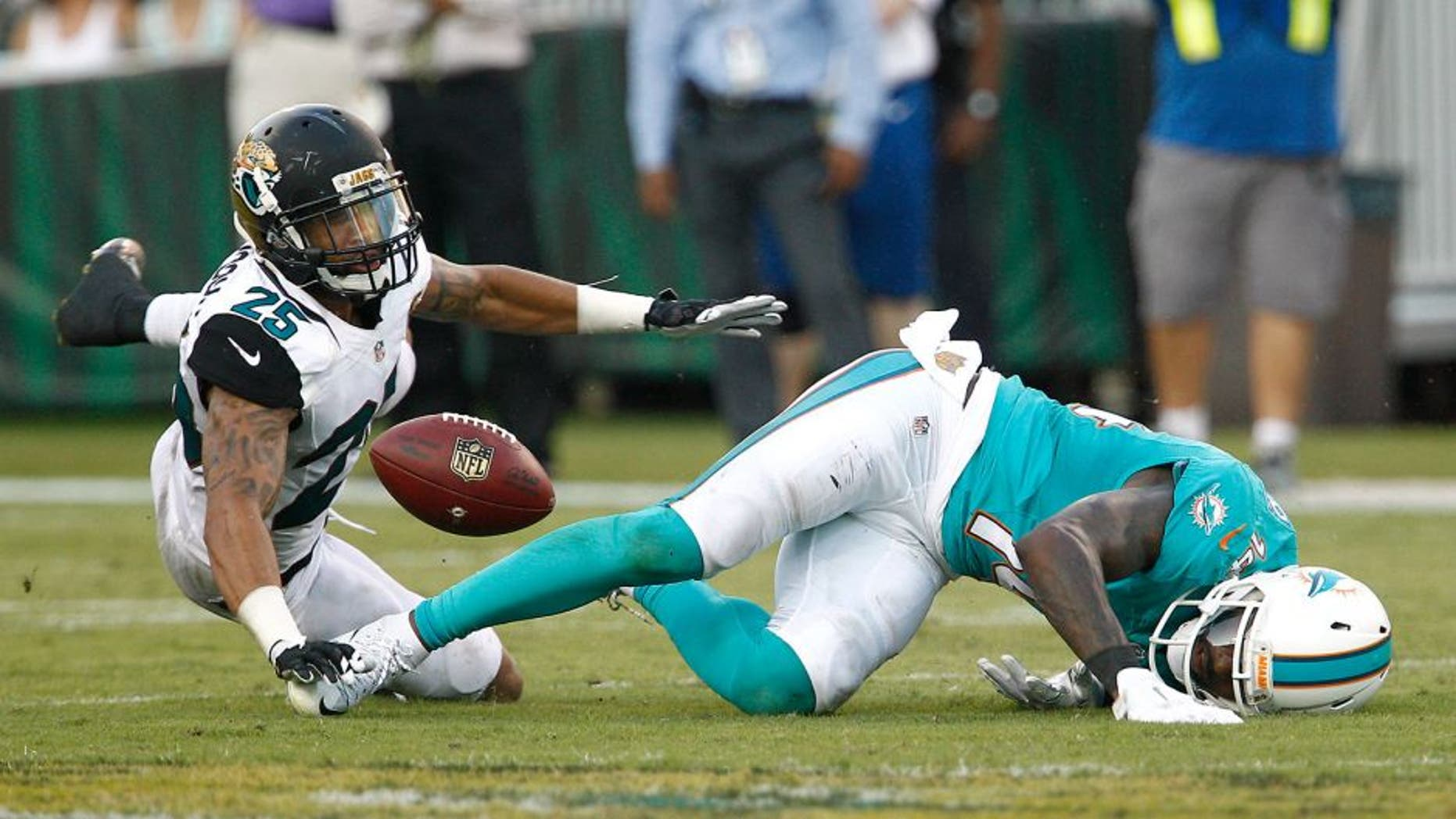 Sep 20, 2015; Jacksonville, FL, USA; Miami Dolphins wide receiver Jarvis Landry (14) can't hold onto the pass under pressure from Jacksonville Jaguars corner back Peyton Thompson (25) during the second half of an NFL Football game at EverBank Field. The Jacksonville Jaguars won 23-20. Mandatory Credit: Reinhold Matay-USA TODAY Sports