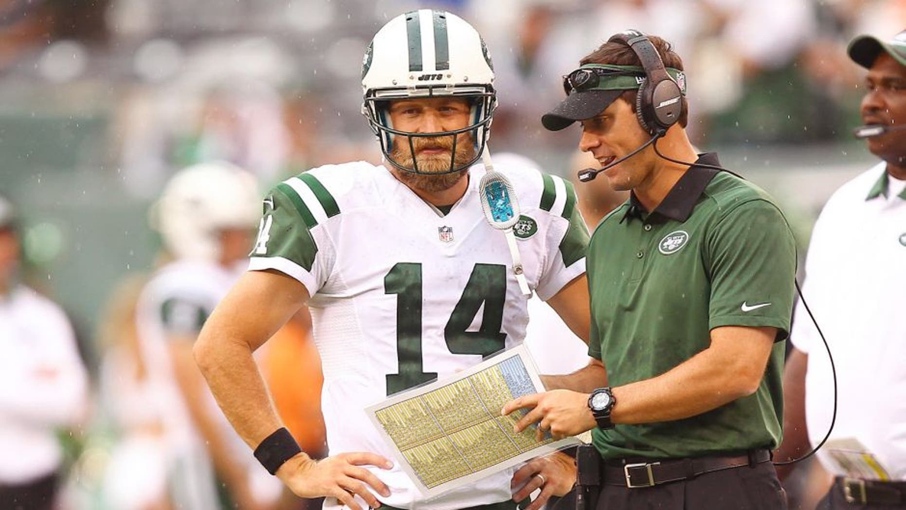 Sep 13, 2015; East Rutherford, NJ, USA; New York Jets quarterback Ryan Fitzpatrick (14) talks with a coach during the second half at MetLife Stadium. Mandatory Credit: Danny Wild-USA TODAY Sports