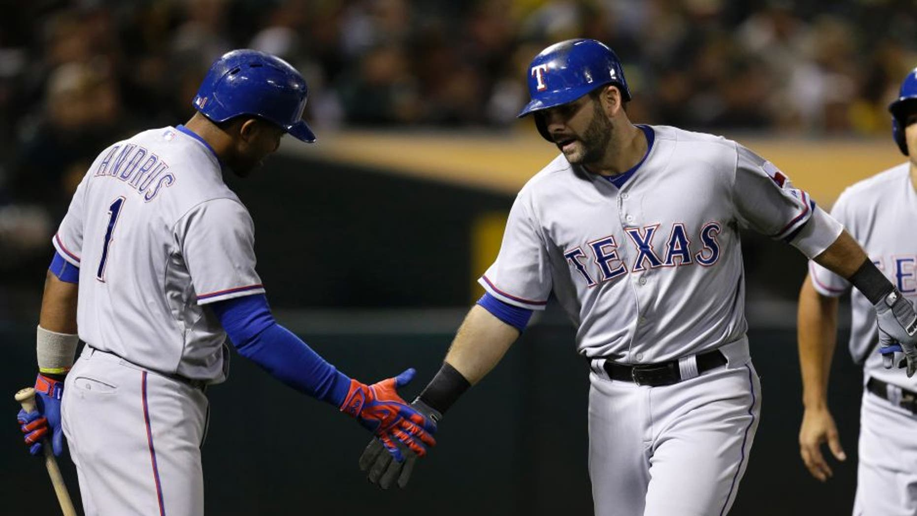 Texas Rangers' Mitch Moreland, center, is congratulated by Elvis Andrus (1) after hitting a two-run home run off Oakland Athletics' Sean Nolin during the sixth inning of a baseball game Tuesday, Sept. 22, 2015, in Oakland, Calif. (AP Photo/Ben Margot)