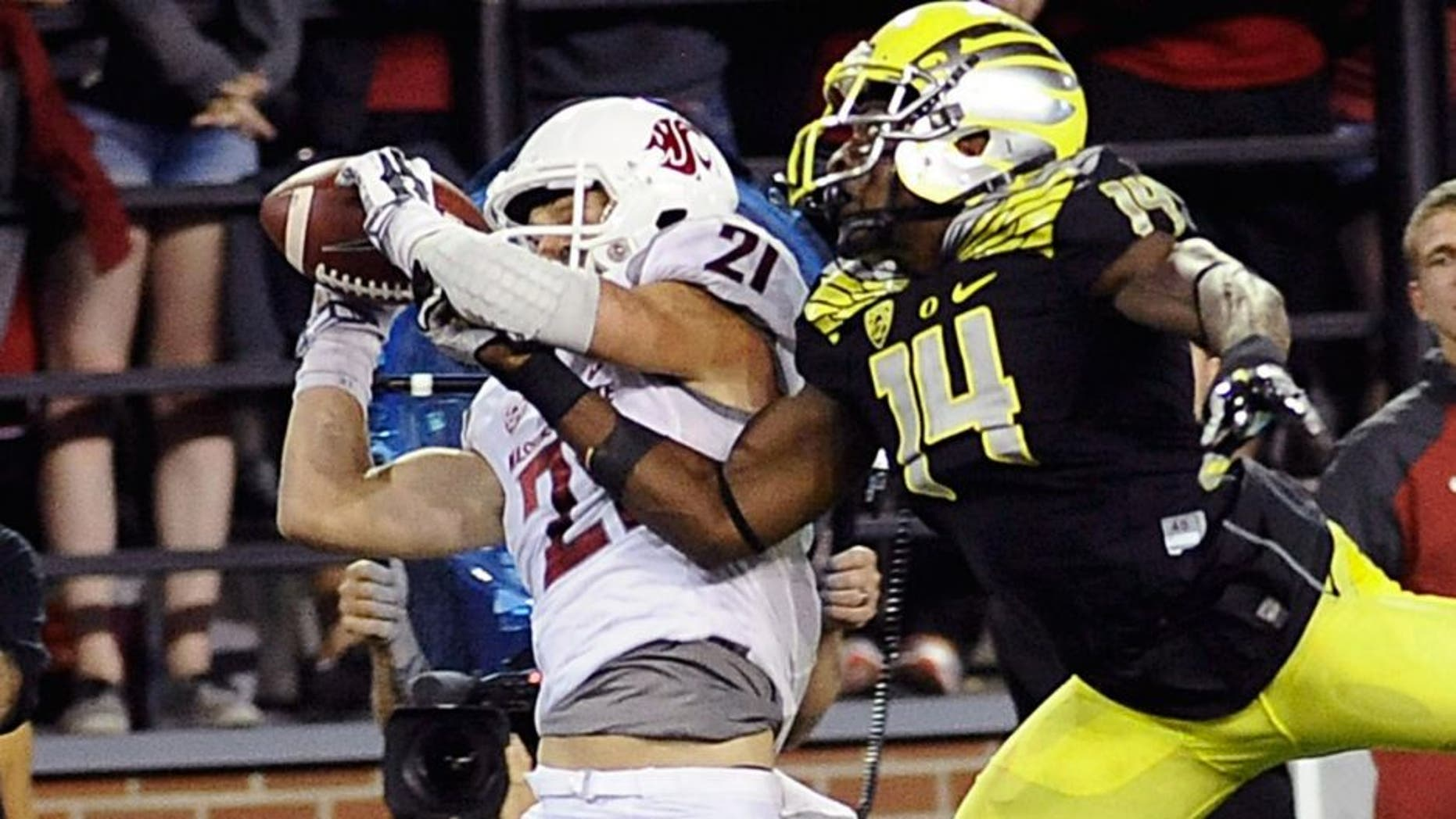 Sep 20, 2014; Pullman, WA, USA; Washington State Cougars wide receiver River Cracraft (21) makes a catch against Oregon Ducks defensive back Ifo Ekpre-Olomu (14) during the second half at Martin Stadium. The Ducks beat Cougars 38-31. Mandatory Credit: James Snook-USA TODAY Sports