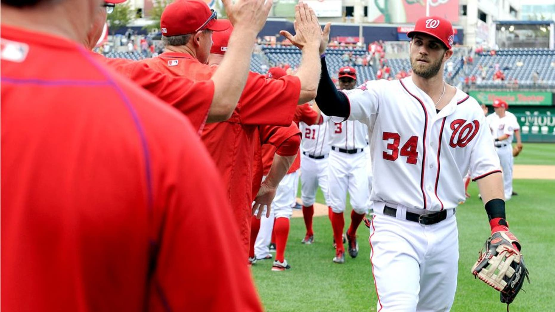 WASHINGTON, DC - SEPTEMBER 20: Bryce Harper #34 of the Washington Nationals celebrates with teammates after a 13-3 victory against the Miami Marlins at Nationals Park on September 20, 2015 in Washington, DC. (Photo by Greg Fiume/Getty Images)
