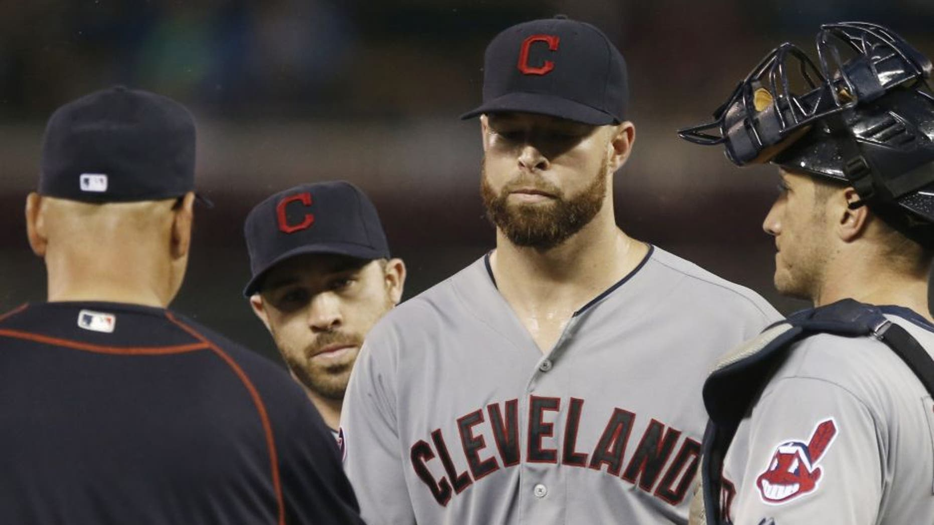 Cleveland Indians pitcher Corey Kluber, center, hands over the ball to manager Terry Francona as he is pulled after giving up four runs to the Minnesota Twins in the fourth inning of a baseball game, Wednesday, Sept. 23, 2015, in Minneapolis.