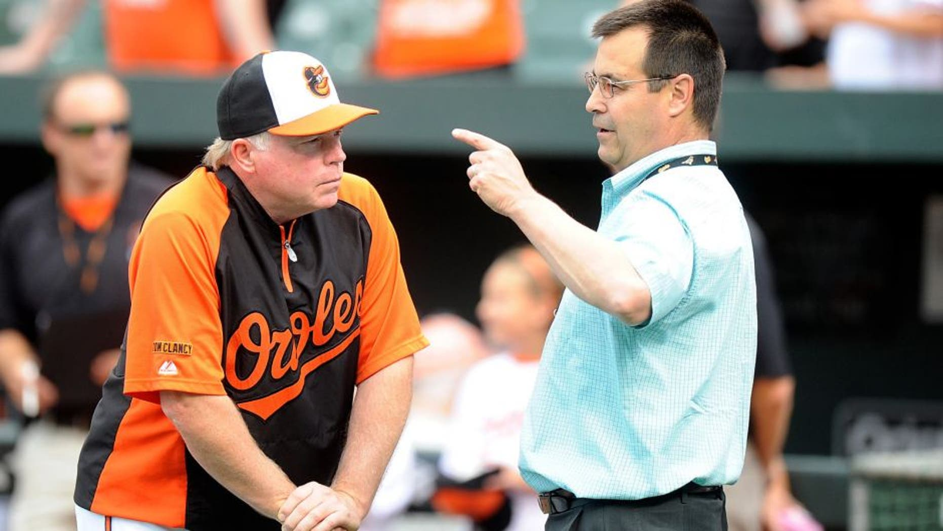 BALTIMORE, MD - AUGUST 02: General Manager Dan Duquette and manager Buck Showalter #26 of the Baltimore Orioles talk before the game against the Seattle Mariners at Oriole Park at Camden Yards on August 2, 2014 in Baltimore, Maryland. (Photo by G Fiume/Getty Images)