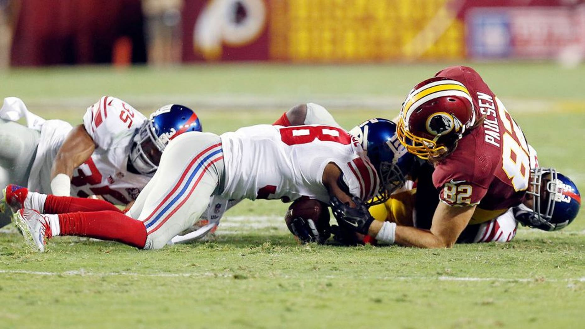 Sep 25, 2014; Landover, MD, USA; New York Giants cornerback Trumaine McBride (38) recovers a fumble by Washington Redskins tight end Logan Paulsen (82) in the second quarter at FedEx Field. Mandatory Credit: Geoff Burke-USA TODAY Sports