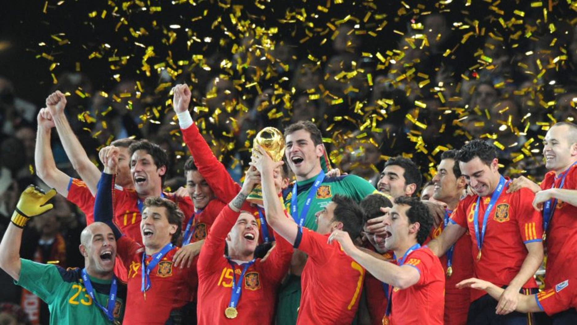 Spain's defender Sergio Ramos (C, L) and Spain's striker David Villa (C, R) hold the trophy as Spain's national football team players celebrate winning the 2010 World Cup football final Netherlands vs. Spain on July 11, 2010 at Soccer City stadium in Soweto, suburban Johannesburg. NO PUSH TO MOBILE / MOBILE USE SOLELY WITHIN EDITORIAL ARTICLE - AFP PHOTO / PEDRO UGARTE (Photo credit should read PEDRO UGARTE/AFP/Getty Images)