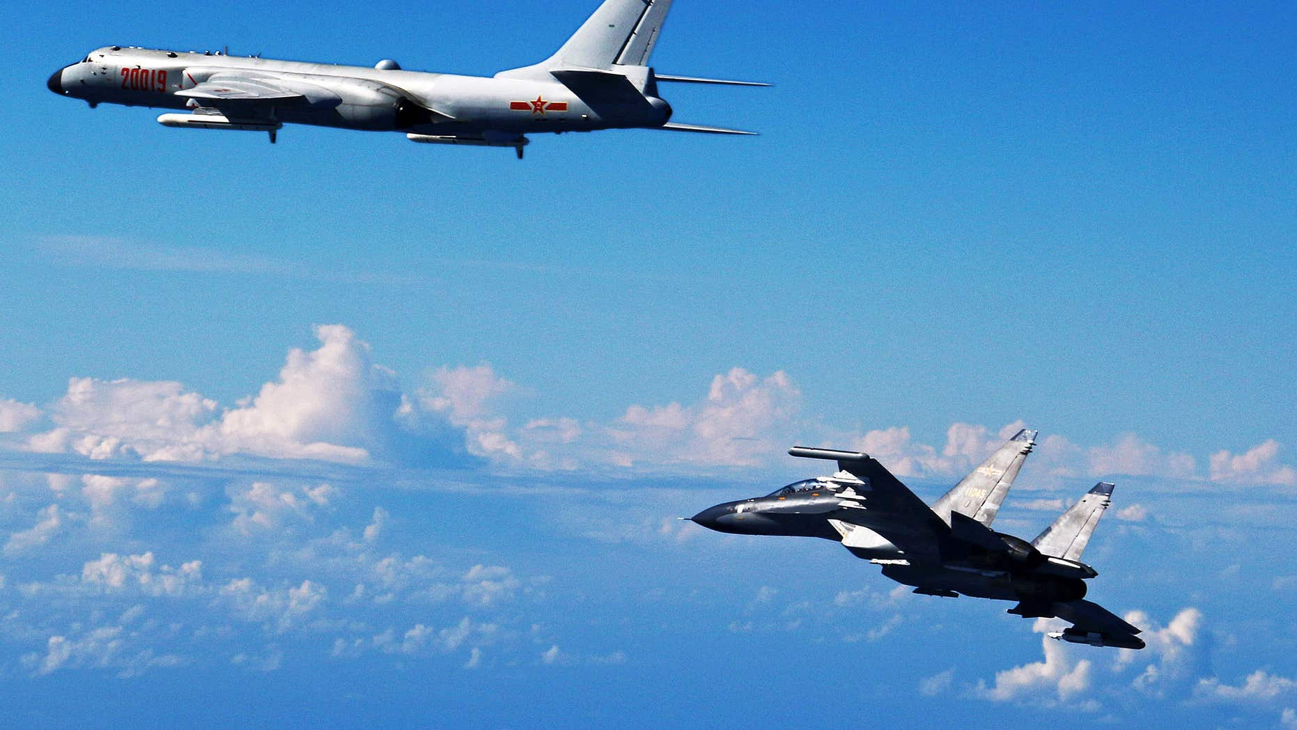 In this Sunday, Sept. 25, 2016, photo released by Xinhua News Agency, Chinese People's Liberation Army Air Force Su-30 fighter, right, flies along with a H-6K bomber as they take part in a drill near the East China Sea.