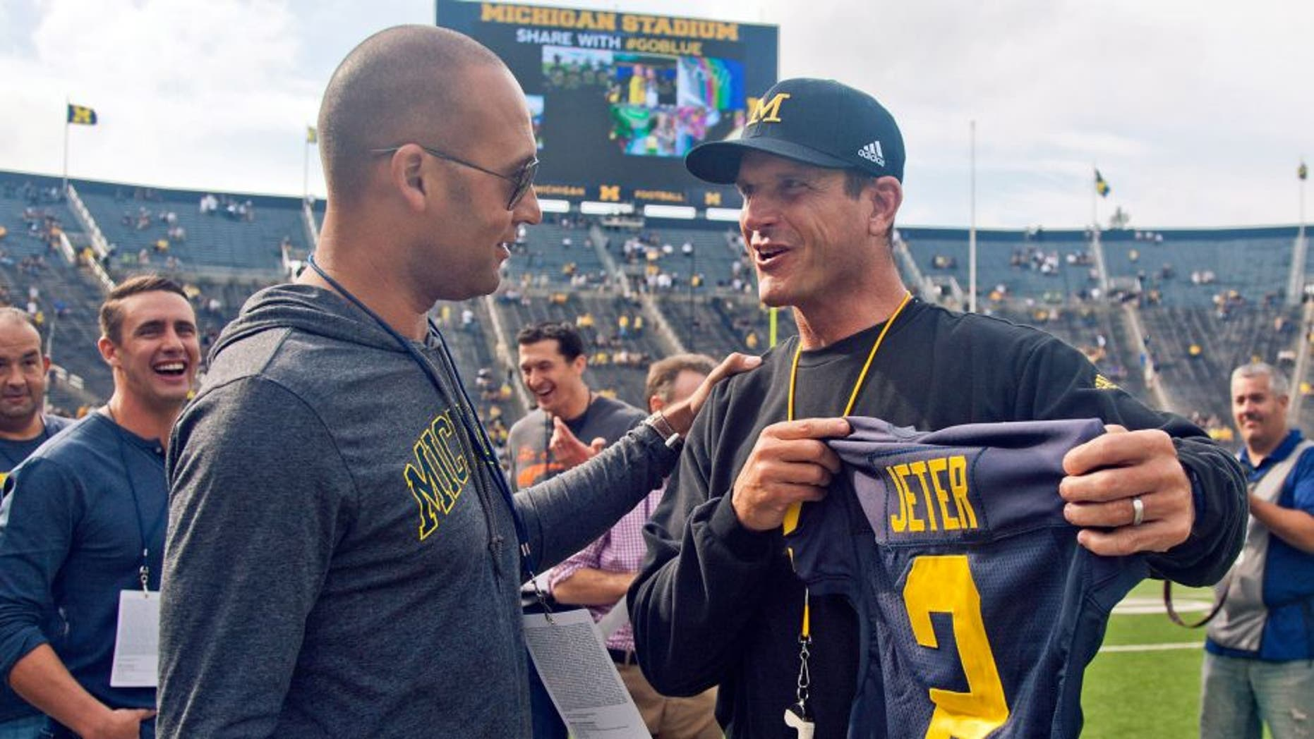 Former New York Yankees baseball player Derek Jeter, left, receives a jersey with his name an No, 2 from Michigan head coach Jim Harbaugh, right, before Michgan's NCAA college football game against BYU in Ann Arbor, Mich., Saturday, Sept. 26, 2015. Jeter graduated high school in Kalamazoo, Mich. and was offered a scholarship to play baseball for Michigan. (AP Photo/Tony Ding)