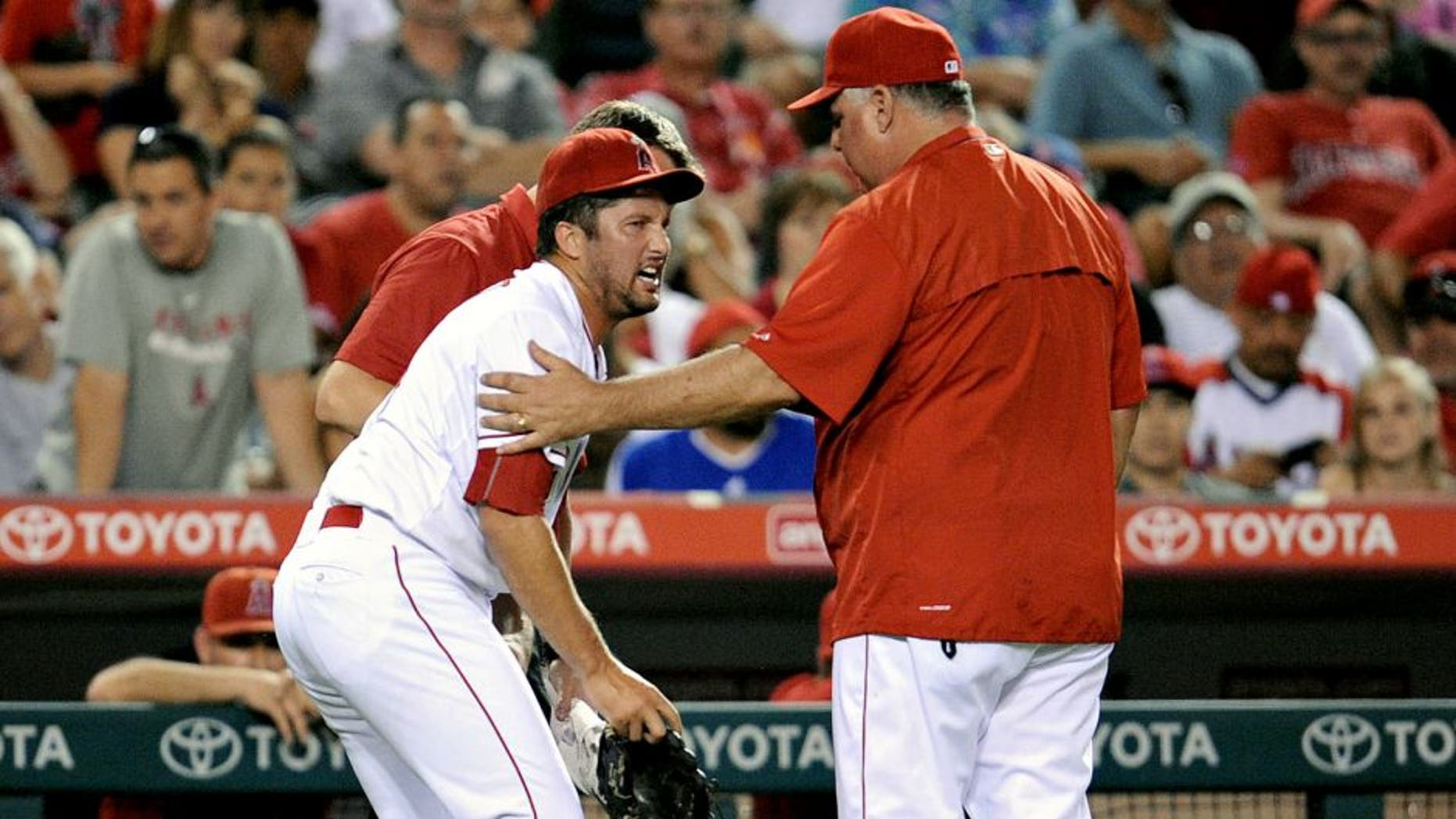 September 26, 2015; Anaheim, CA, USA; Los Angeles Angels relief pitcher Huston Street (16) reacts as he is helped by the team trainer and manager Mike Scioscia (14) after suffering an apparent injury in the ninth inning against the Seattle Mariners at Angel Stadium of Anaheim. Mandatory Credit: Gary A. Vasquez-USA TODAY Sports