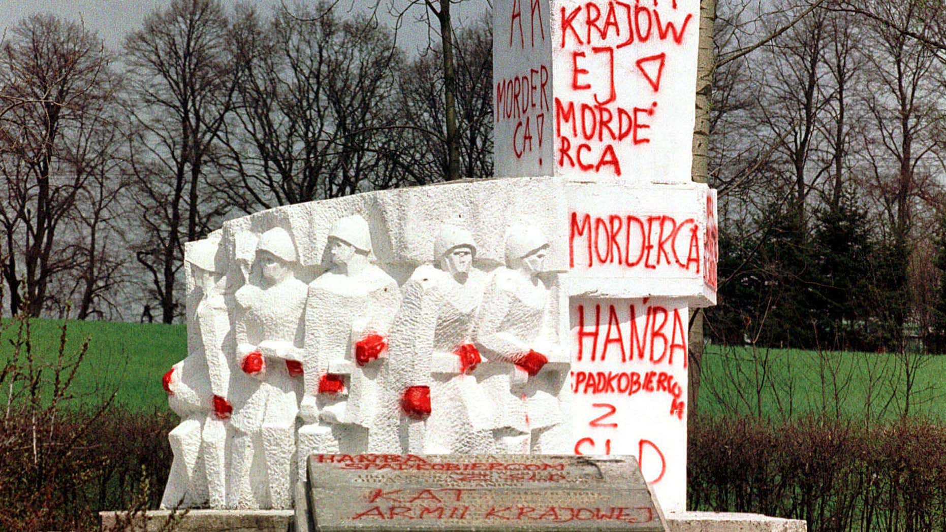 "FILE- In this April 30, 2001 file photo taken in Pieniezno, Poland, graffiti with insults like ""Murderer"" and ""Shame"" can be seen on a memorial to Soviet General Ivan Chernyakhovsky, who is considered a symbol of the imposition of communism in Poland, but a national hero in Russia."